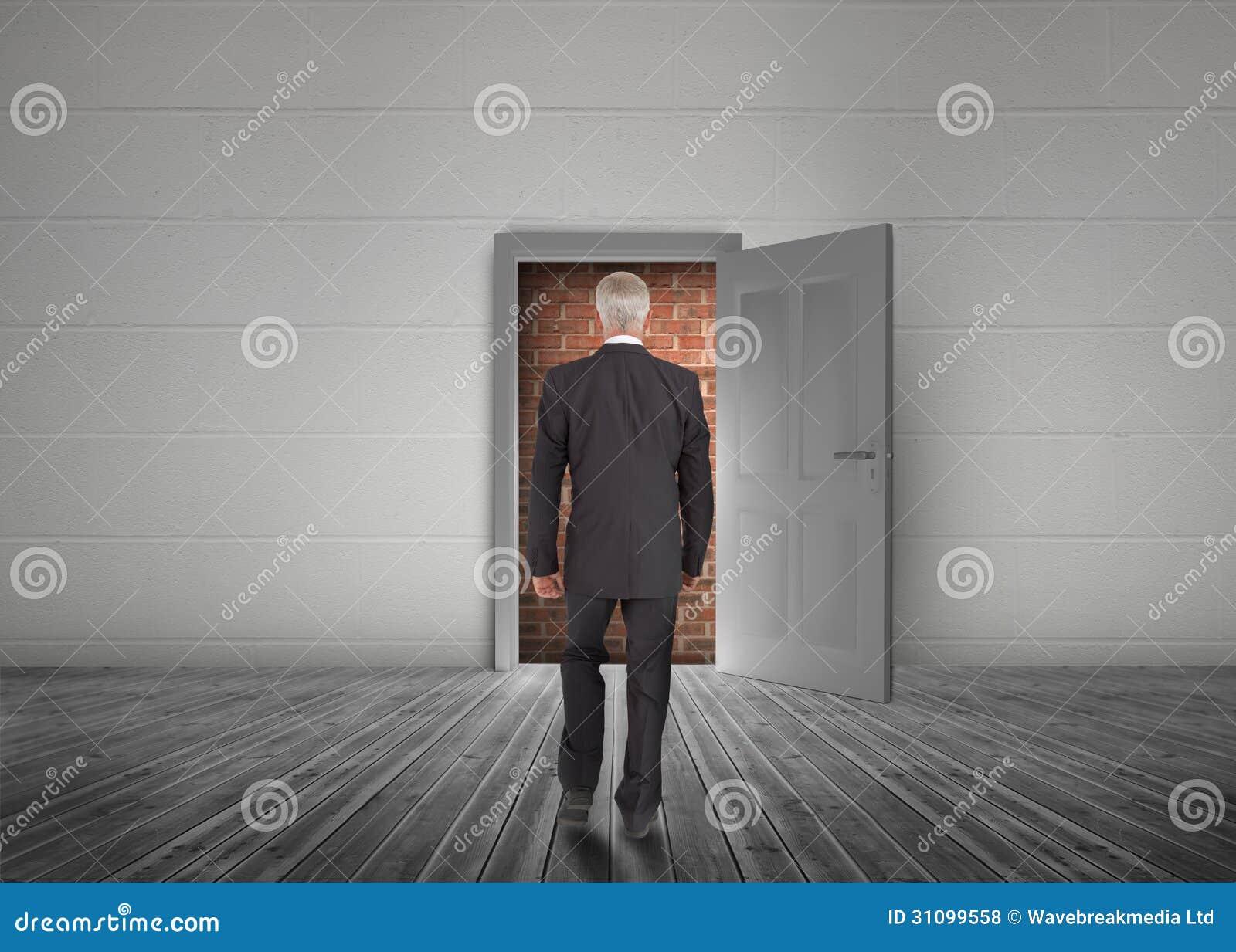 Businessman walking towards door open but blocked by red brick w