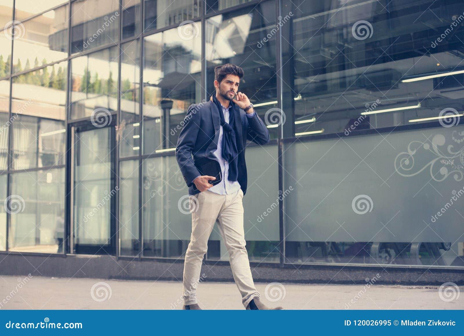 Businessman walking trough street and holding digital t