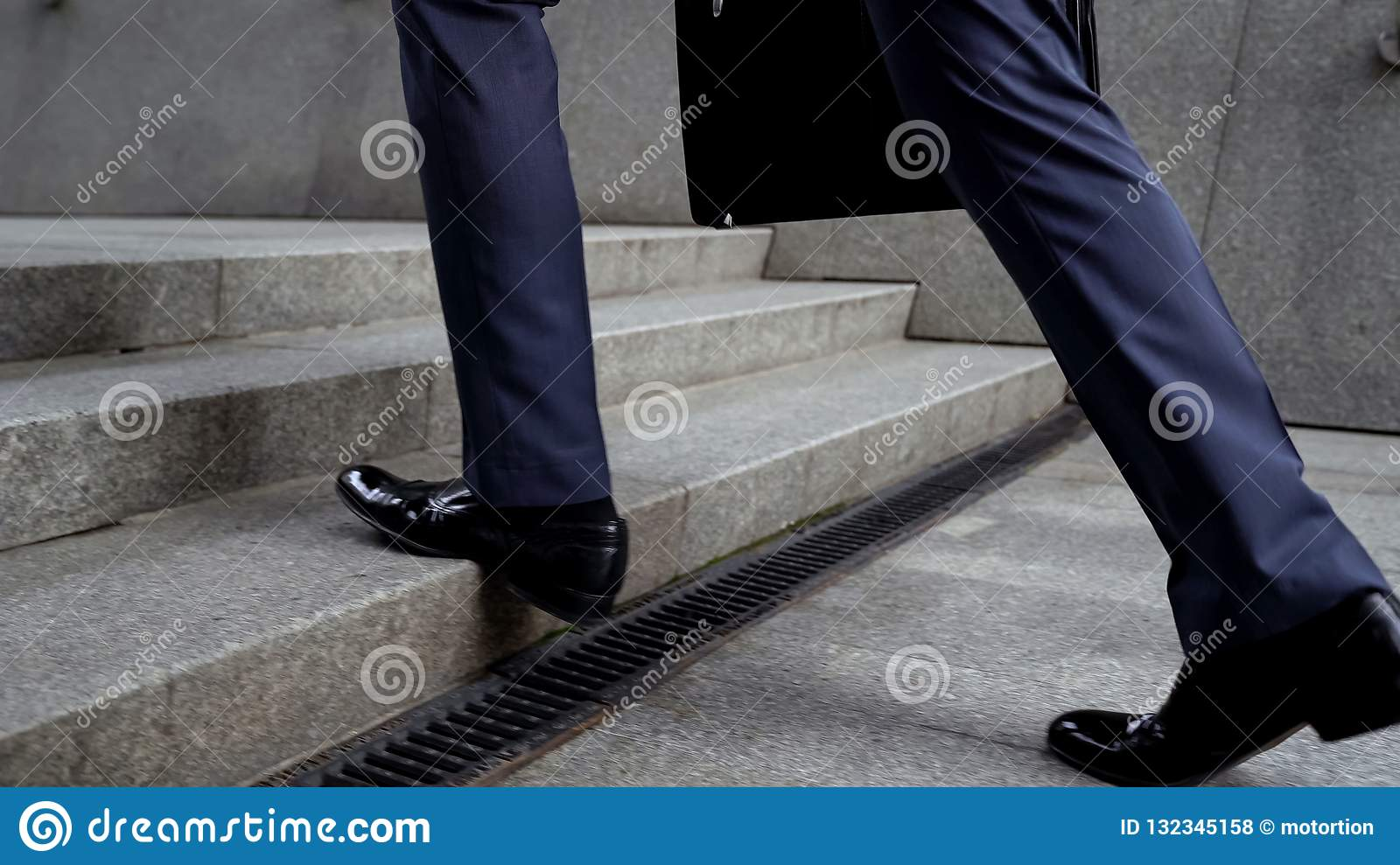 Businessman walking up stairs, success in career concept, promotion, closeup