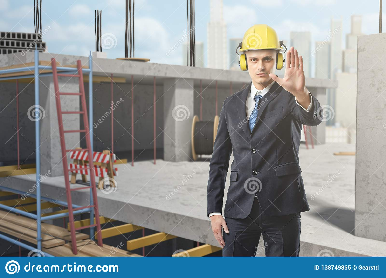Businessman wearing yellow safety helmet and showing stop gesture at construction site