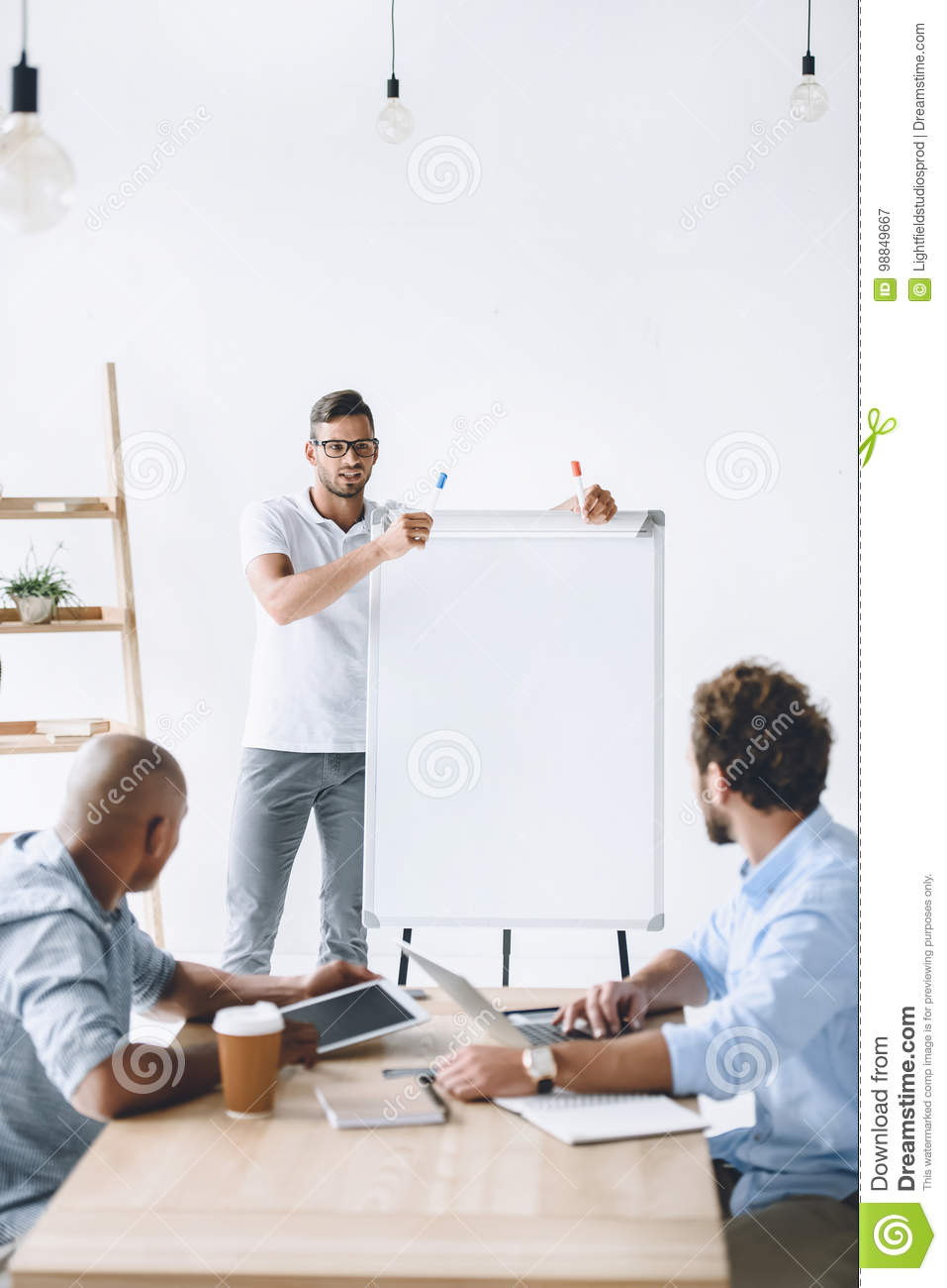 Businessman at white board making presentation to colleagues