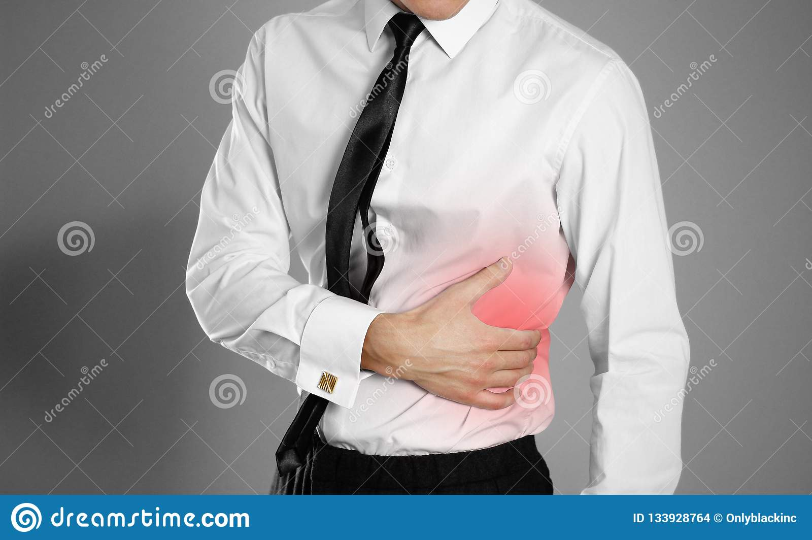 Businessman in a white shirt and tie holding his side. Pain in t