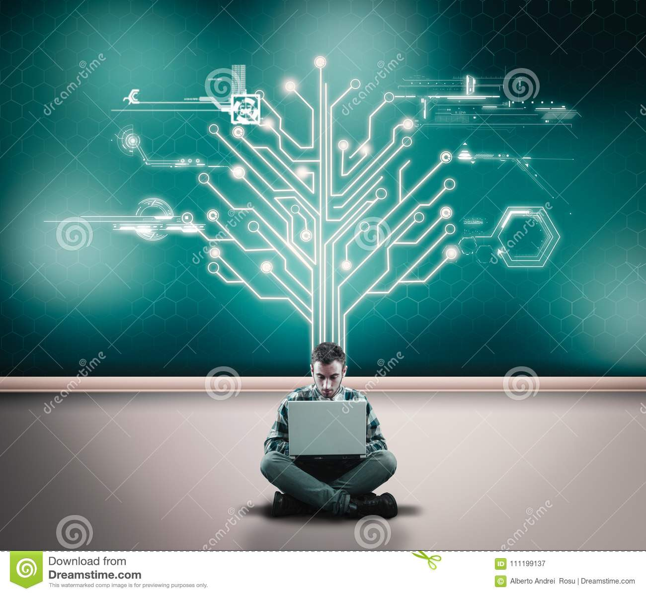 Businessman working on his laptop in front of a wall with a circuit board tree