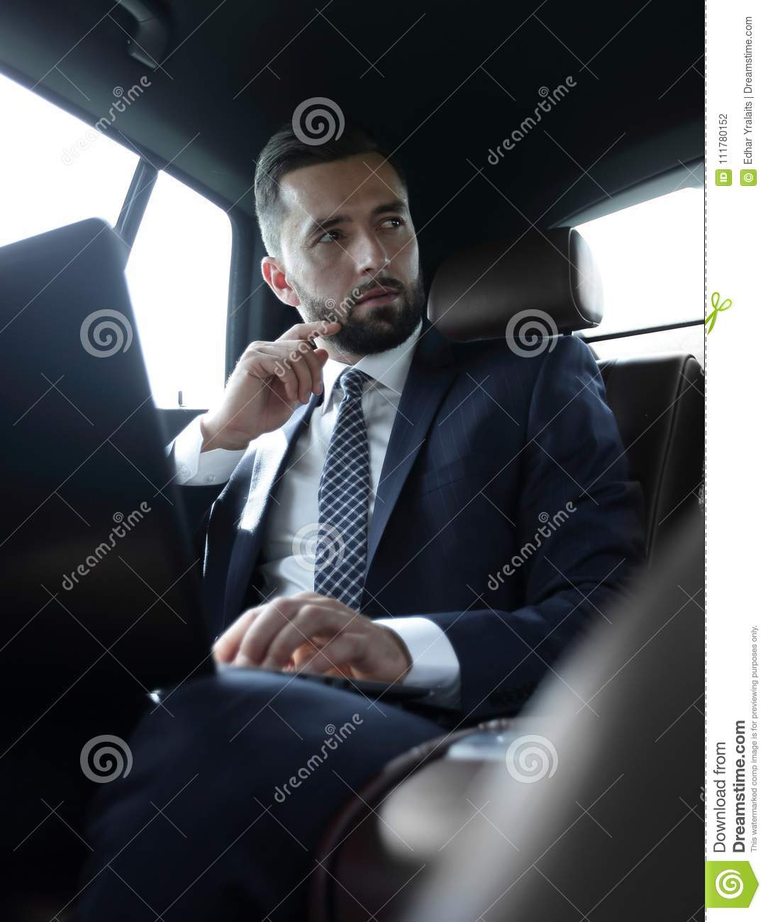 Businessman working with laptop and looking out the window of a car