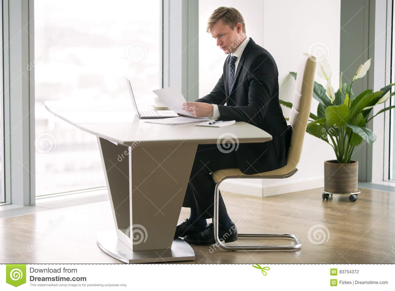 Businessman working with laptop and paper at the modern desk