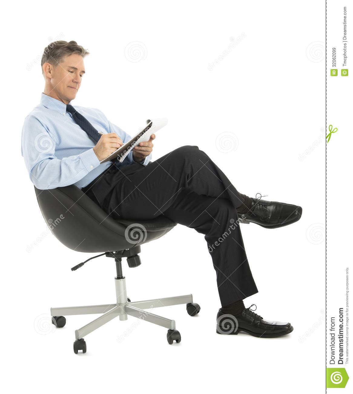 Businessman writing in note pad while sitting on office for Sitting chairs