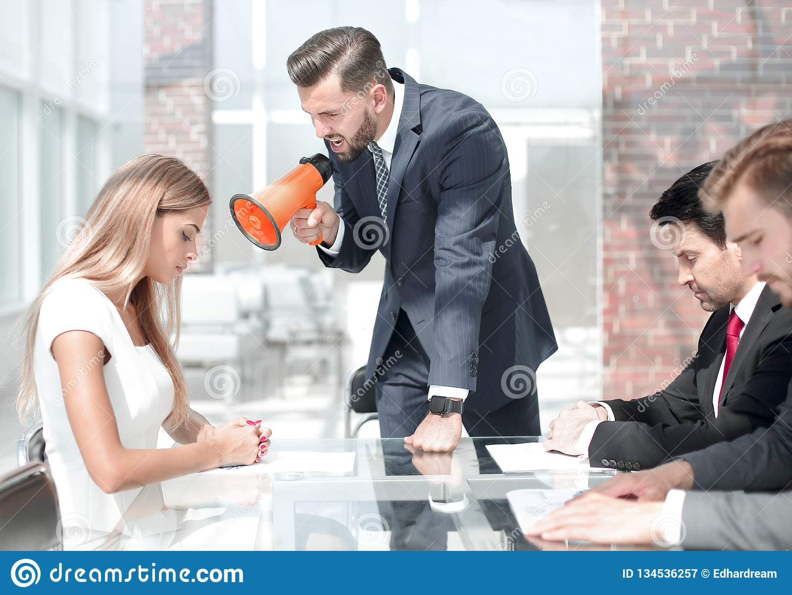Businessman yelling at a female employee through a megaphone. Management concept royalty free stock photography
