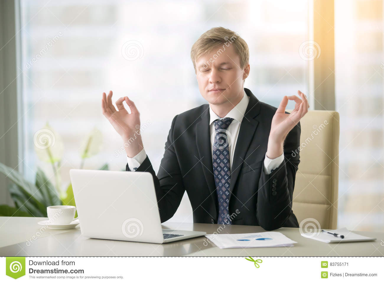 Businessman in yoga pose in the office