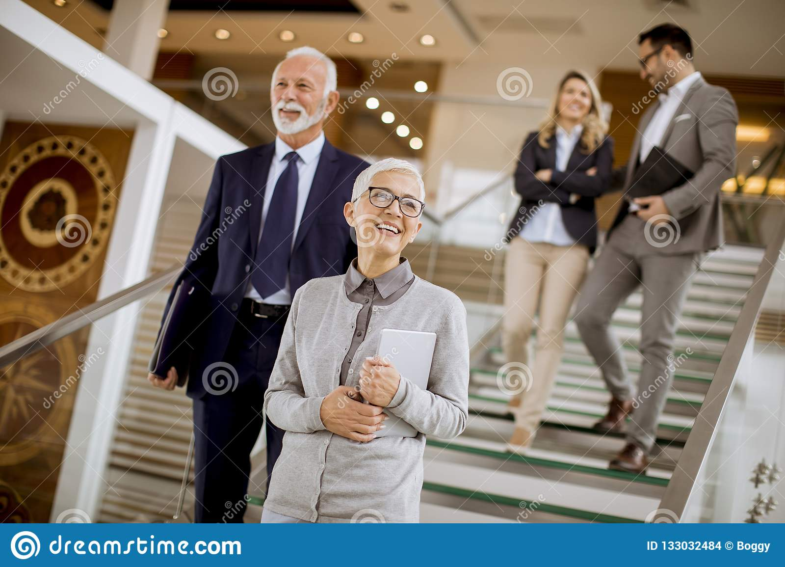 Businessmen and businesswomen walking and taking stairs in an of
