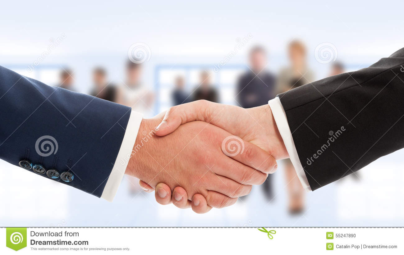 Businessmen hand shake with business people in background
