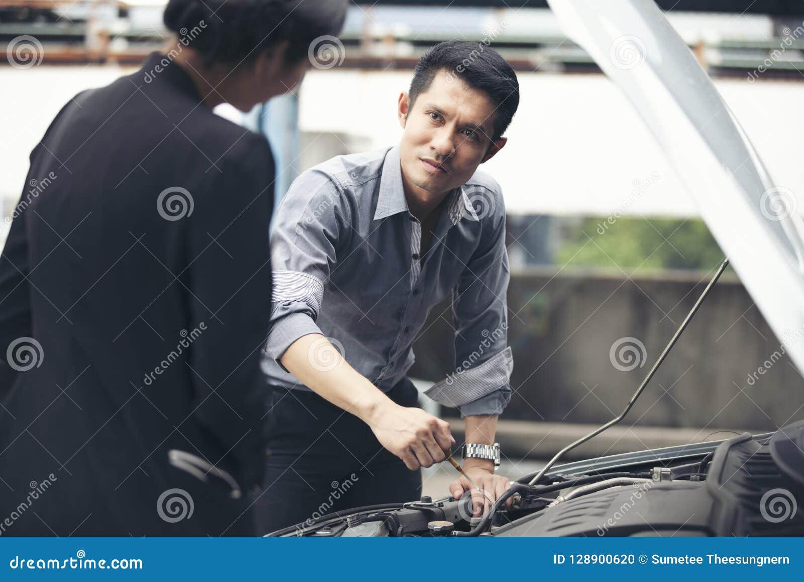 Businessmen help businesswomen check and repair broken cars