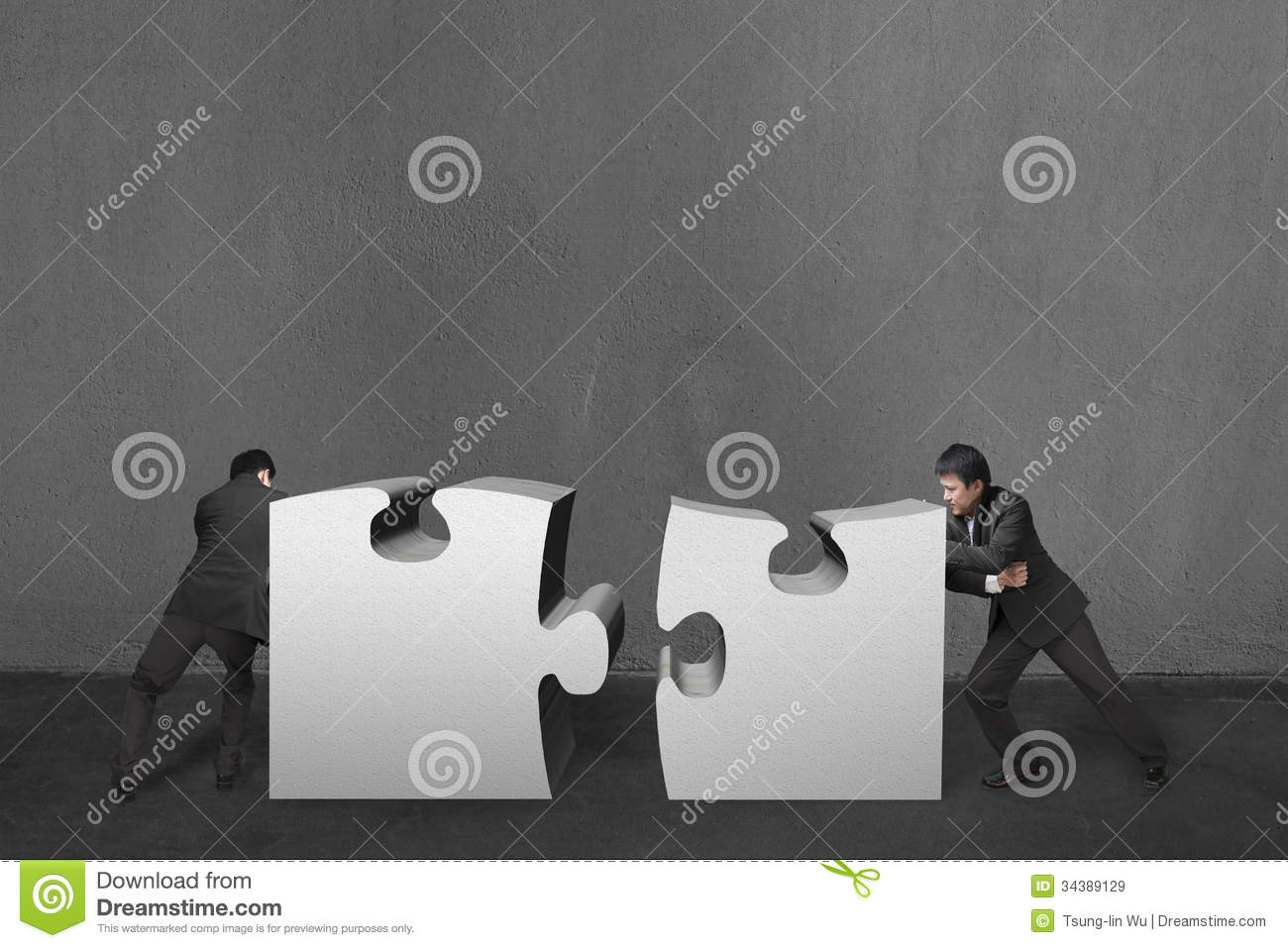 Concrete Push Wall Design : Businessmen push two heavy puzzles together in concrete