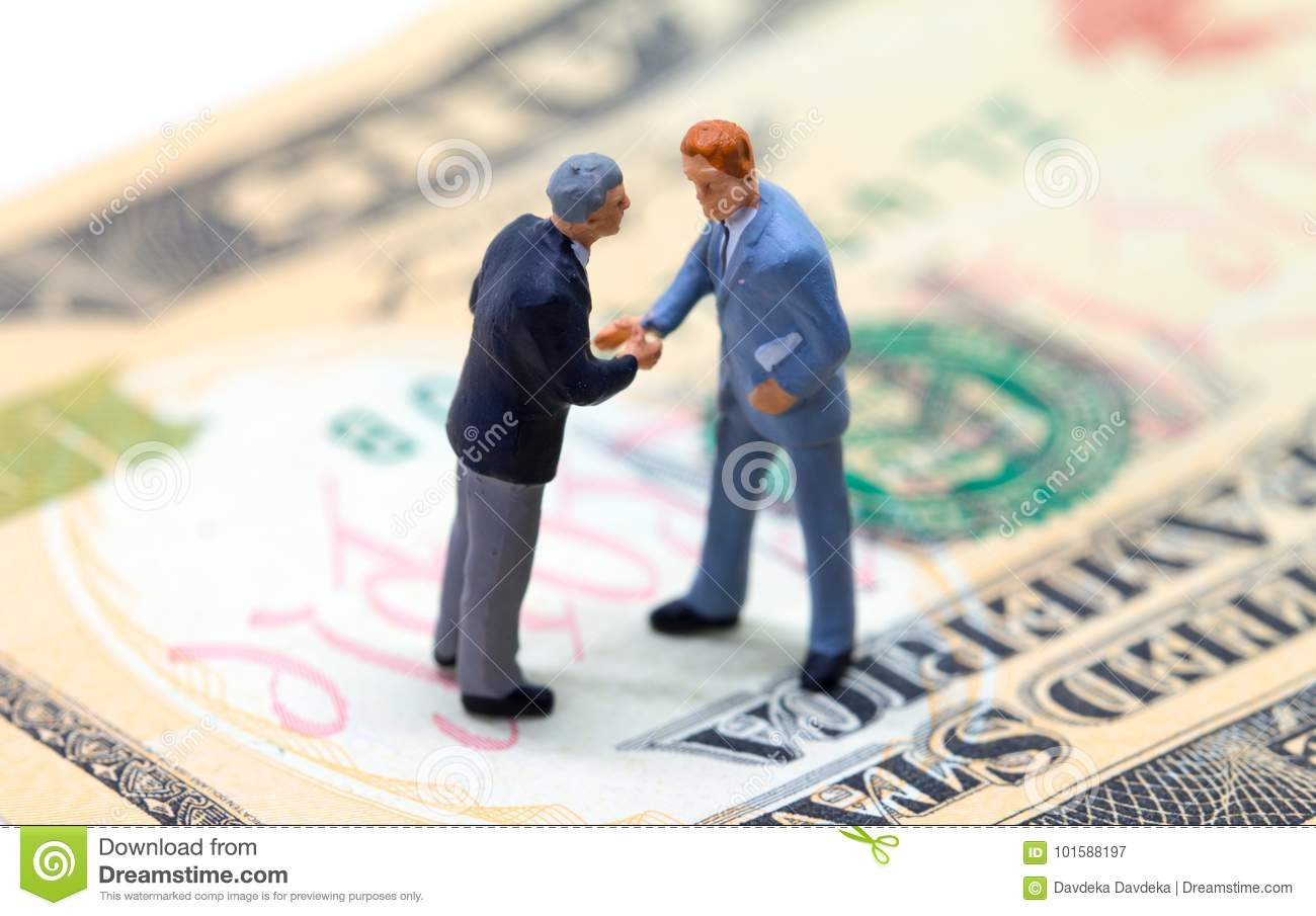Businessmen shaking hands on american dollar. Tiny businessmen figurines on money background.