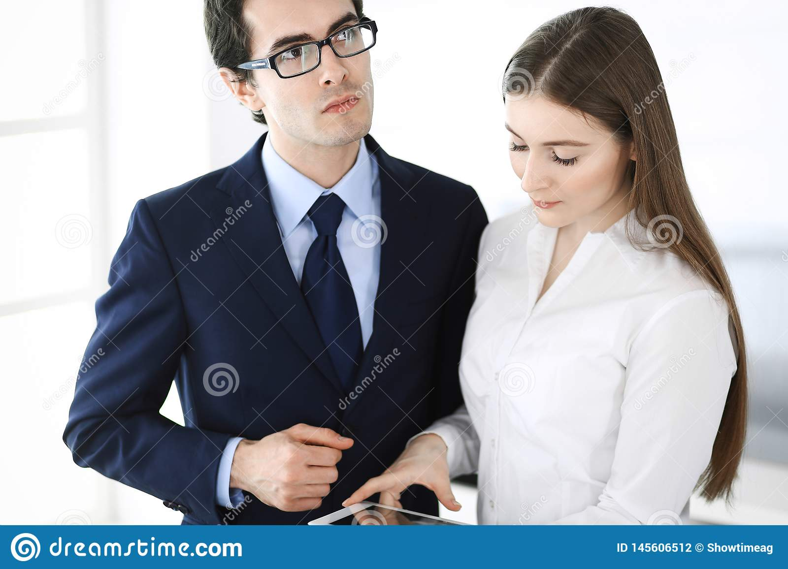 Businessmen and woman using tablet computer in modern office. Colleagues or company managers at workplace. Partners