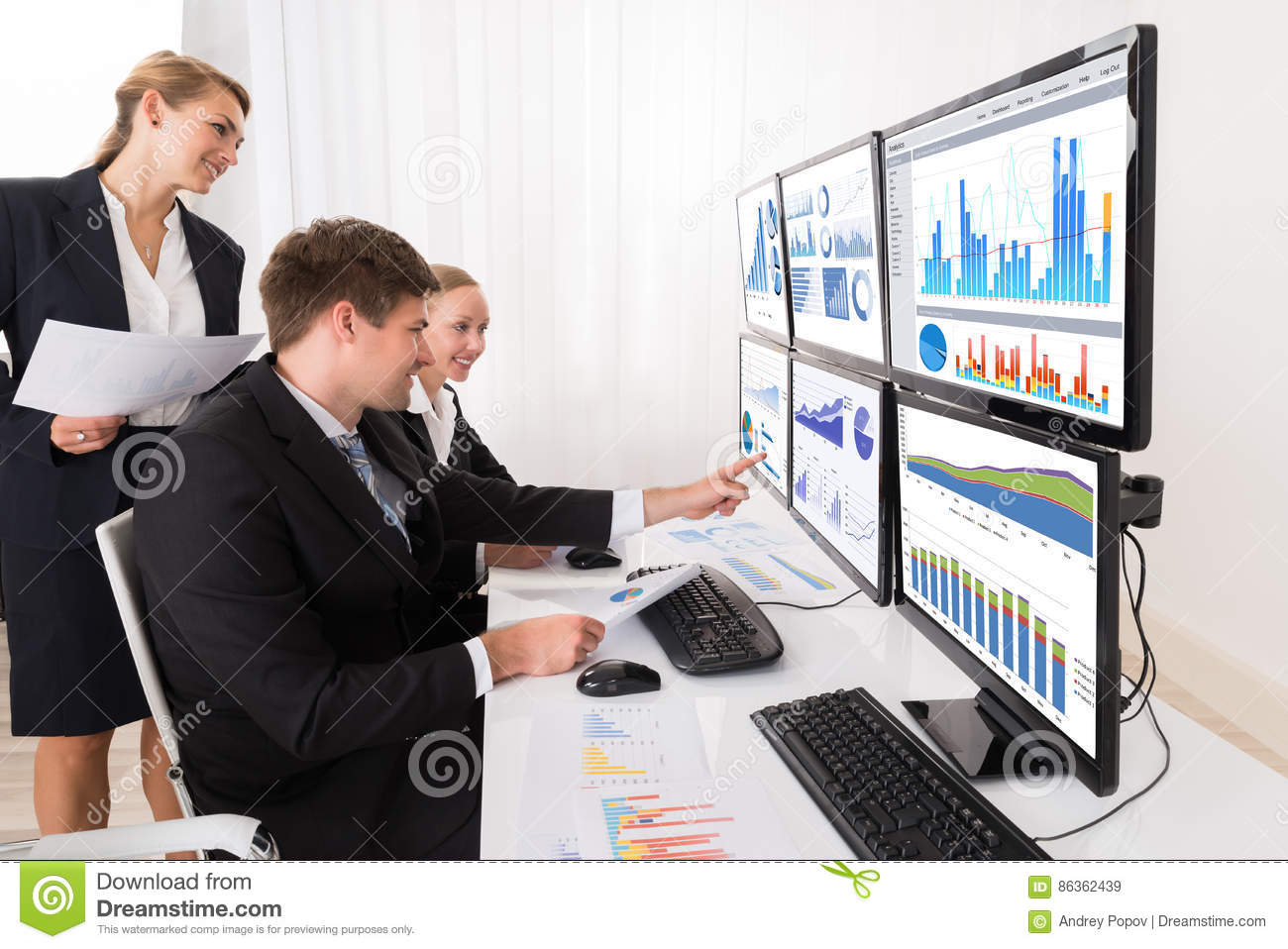 Businesspeople Analyzing Graphs On Multiple Computers