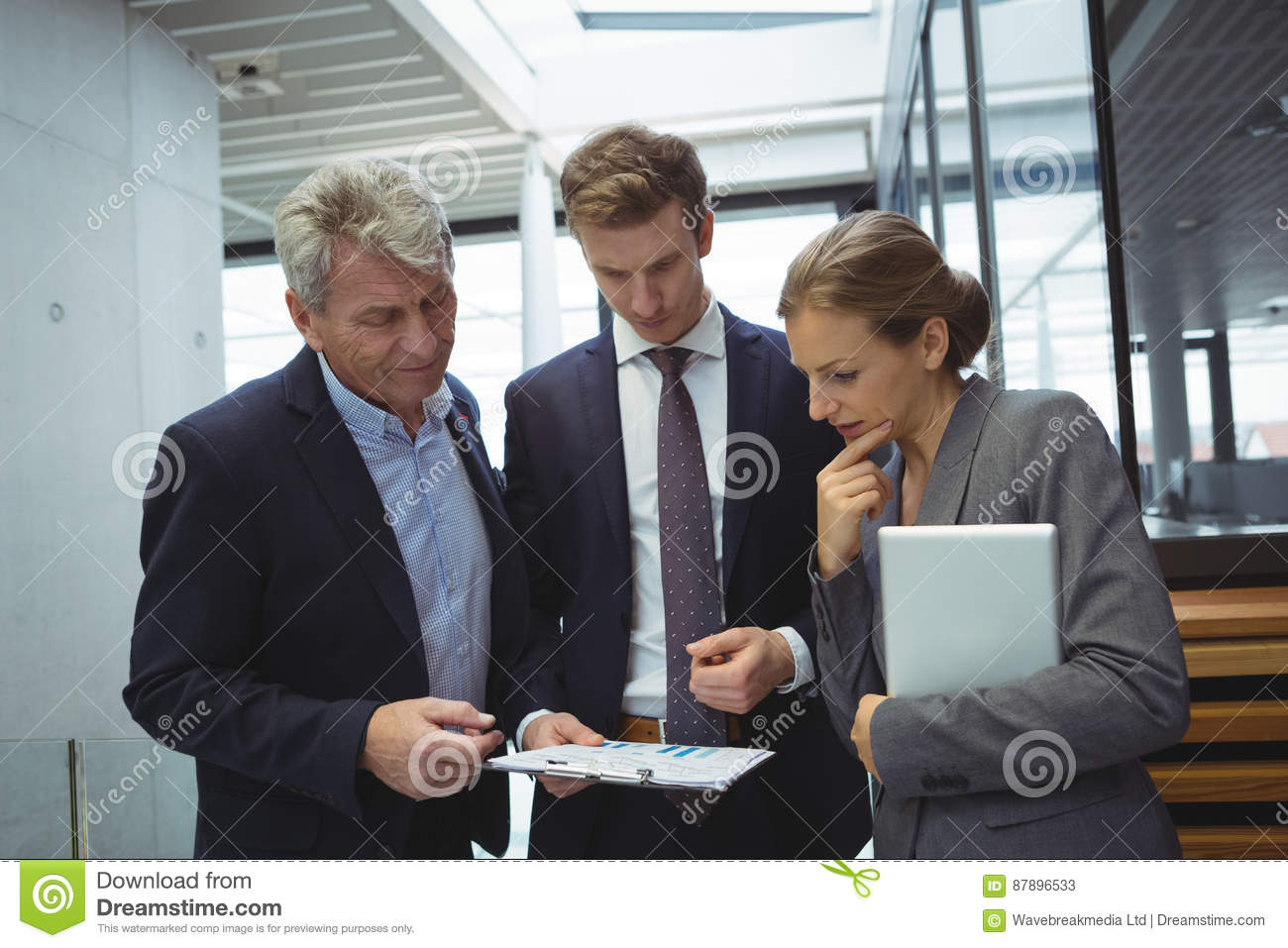 businesspeople looking at paper documents in the corridor stock image image 87896533. Black Bedroom Furniture Sets. Home Design Ideas