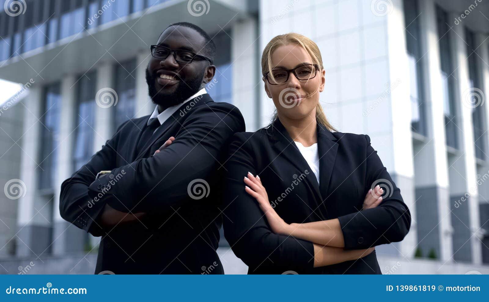 Businesspeople med korsade armar som ser kameran, karriär och lyckad framtid