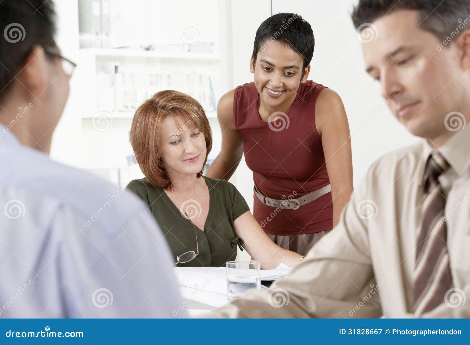 Businesspeople som diskuterar runt om kontorsskrivbordet