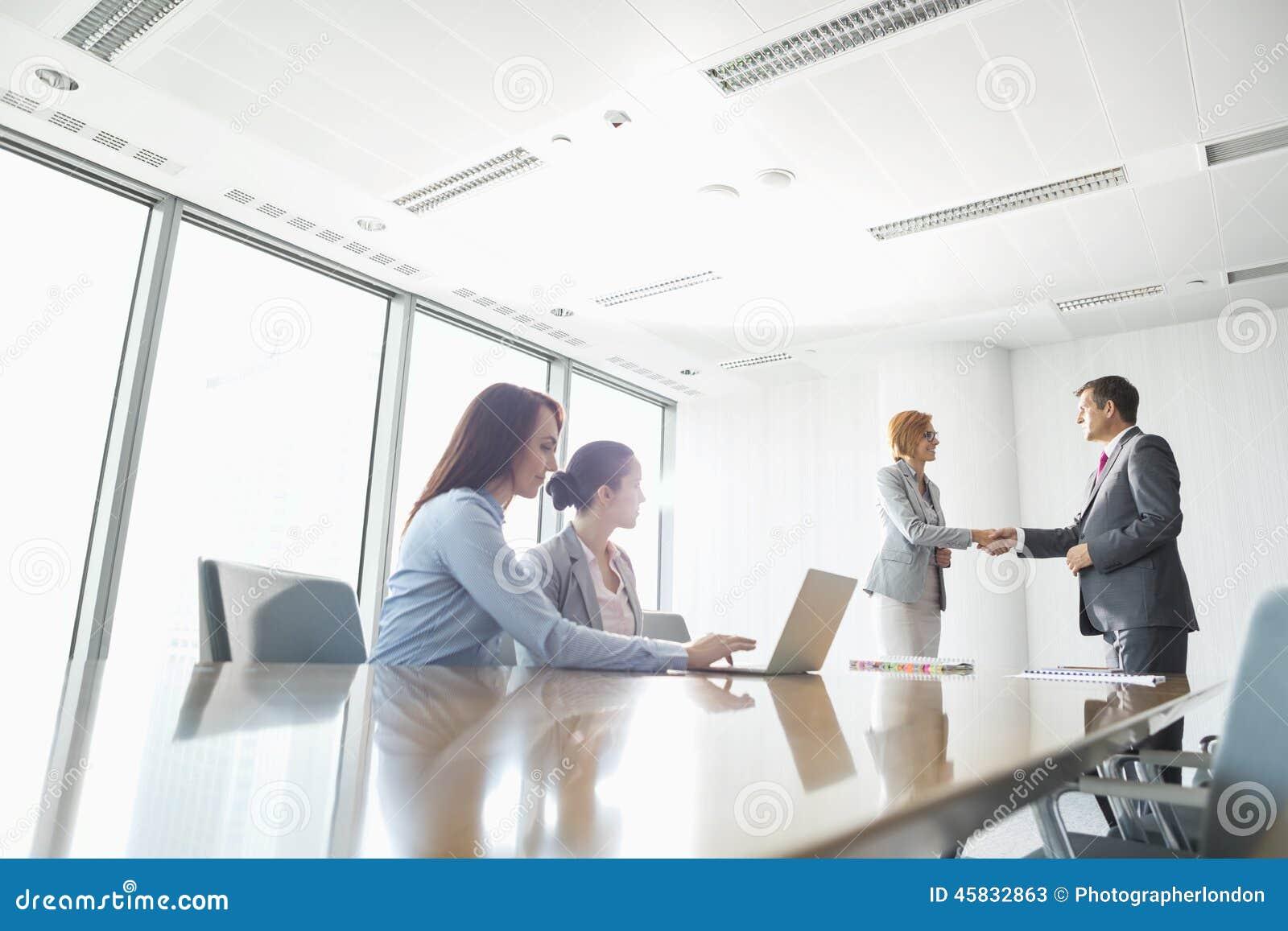 Businesspeople som skakar händer i bräderum