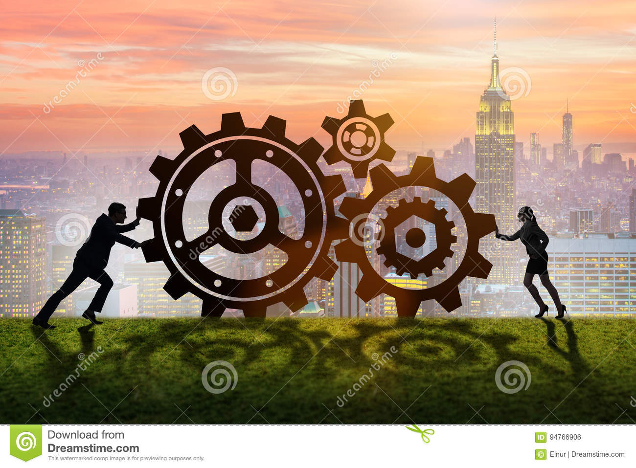 The businesspeople in teamwork example with cogwheels stock photo.