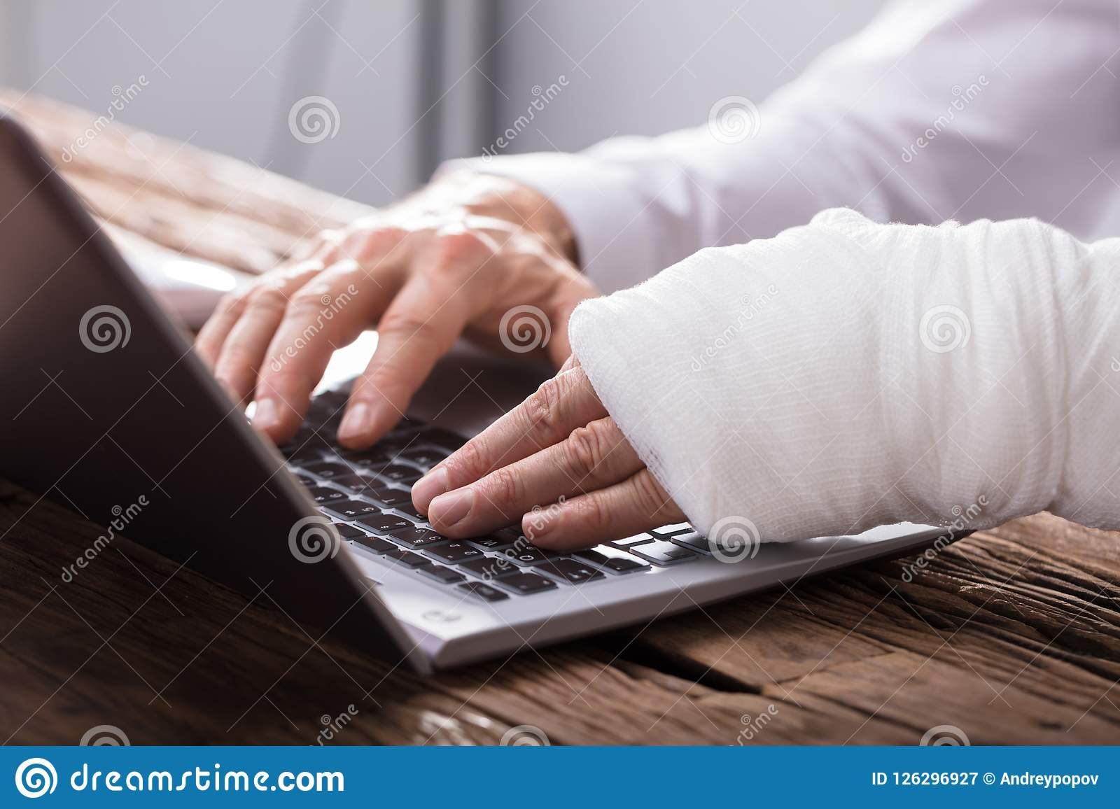 Businessperson With Hand Injury Using Laptop