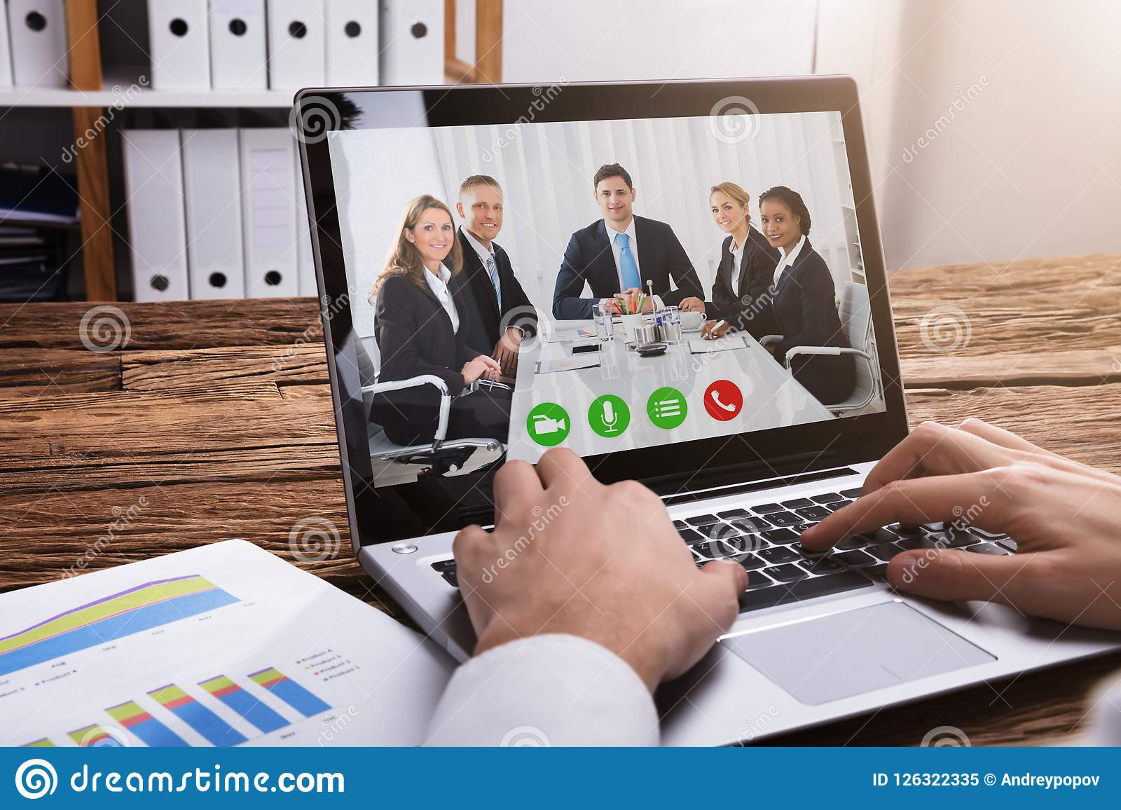 Businessperson Video Conferencing With Colleagues On Laptop