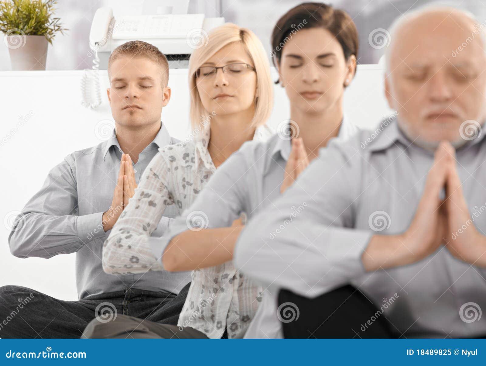 Businessteam, das Yogaübung tut