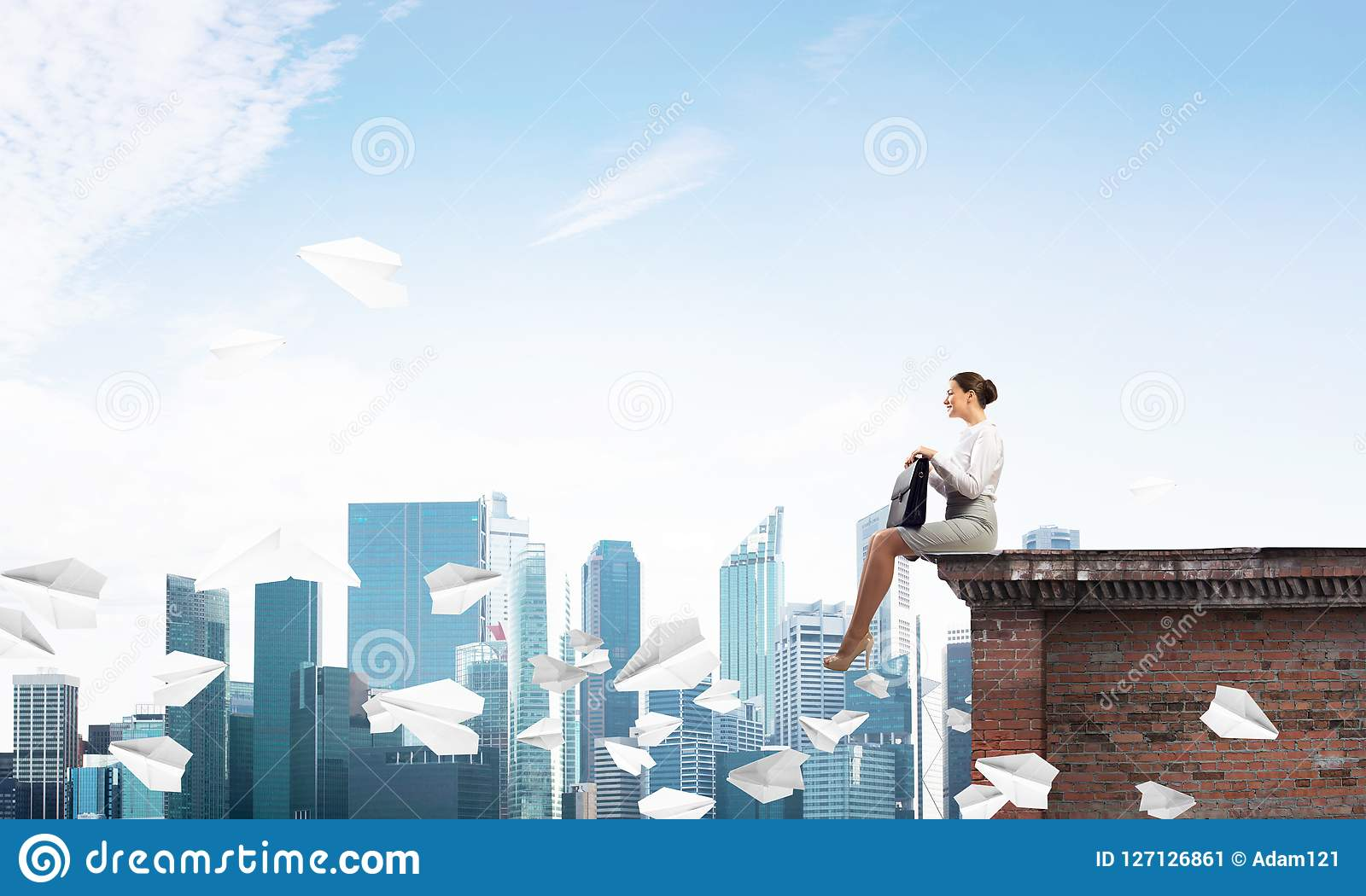 Businesswoman or accountant on building top and paper planes flying around. Mixed media