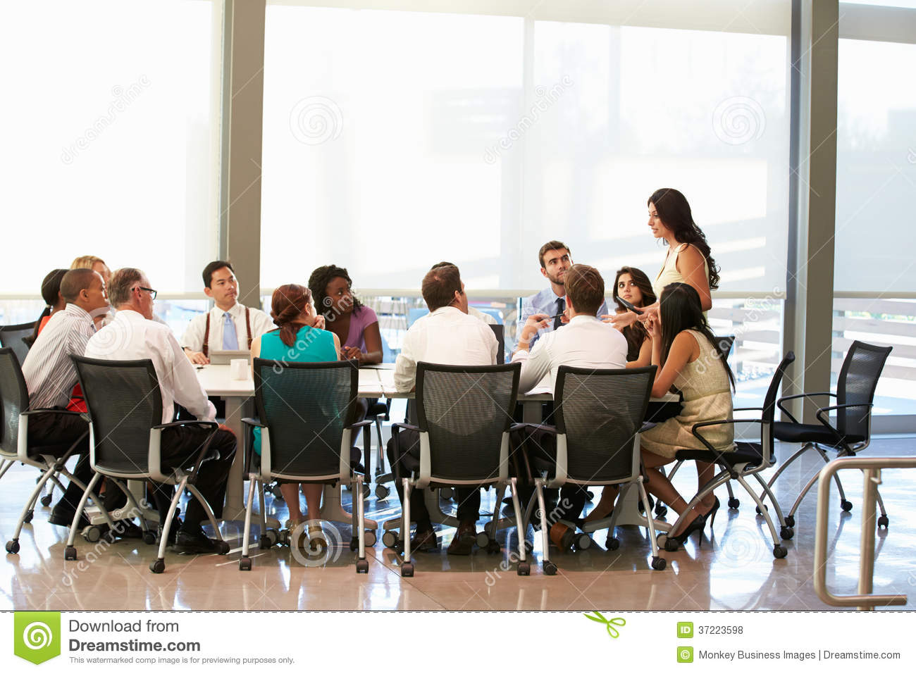 Astounding Businesswoman Addressing Meeting Around Boardroom Table Beutiful Home Inspiration Ommitmahrainfo