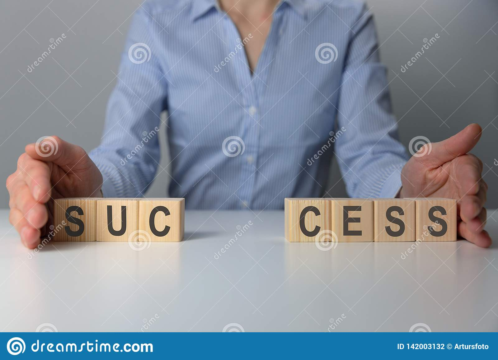 Businesswoman adjusting `success` word made of wooden blocks. Success word from wooden blocks on desk. Business success