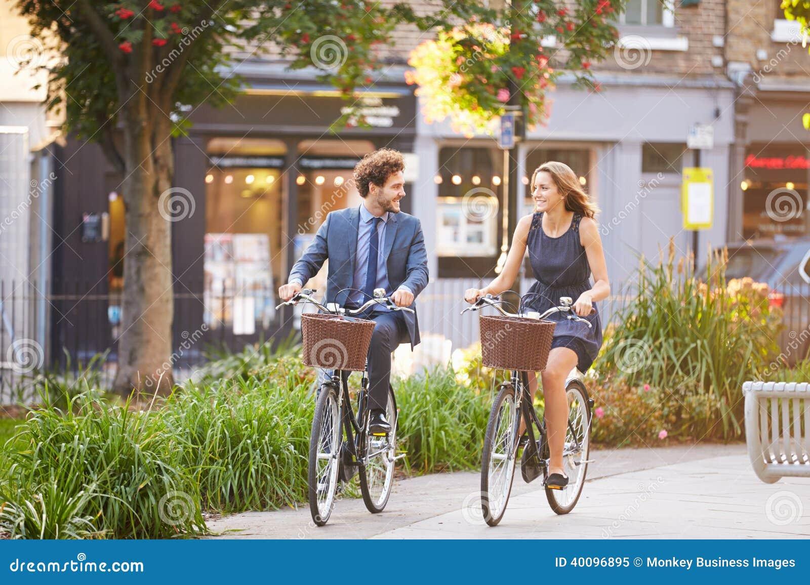 Businesswoman And Businessman Riding Bike Through City