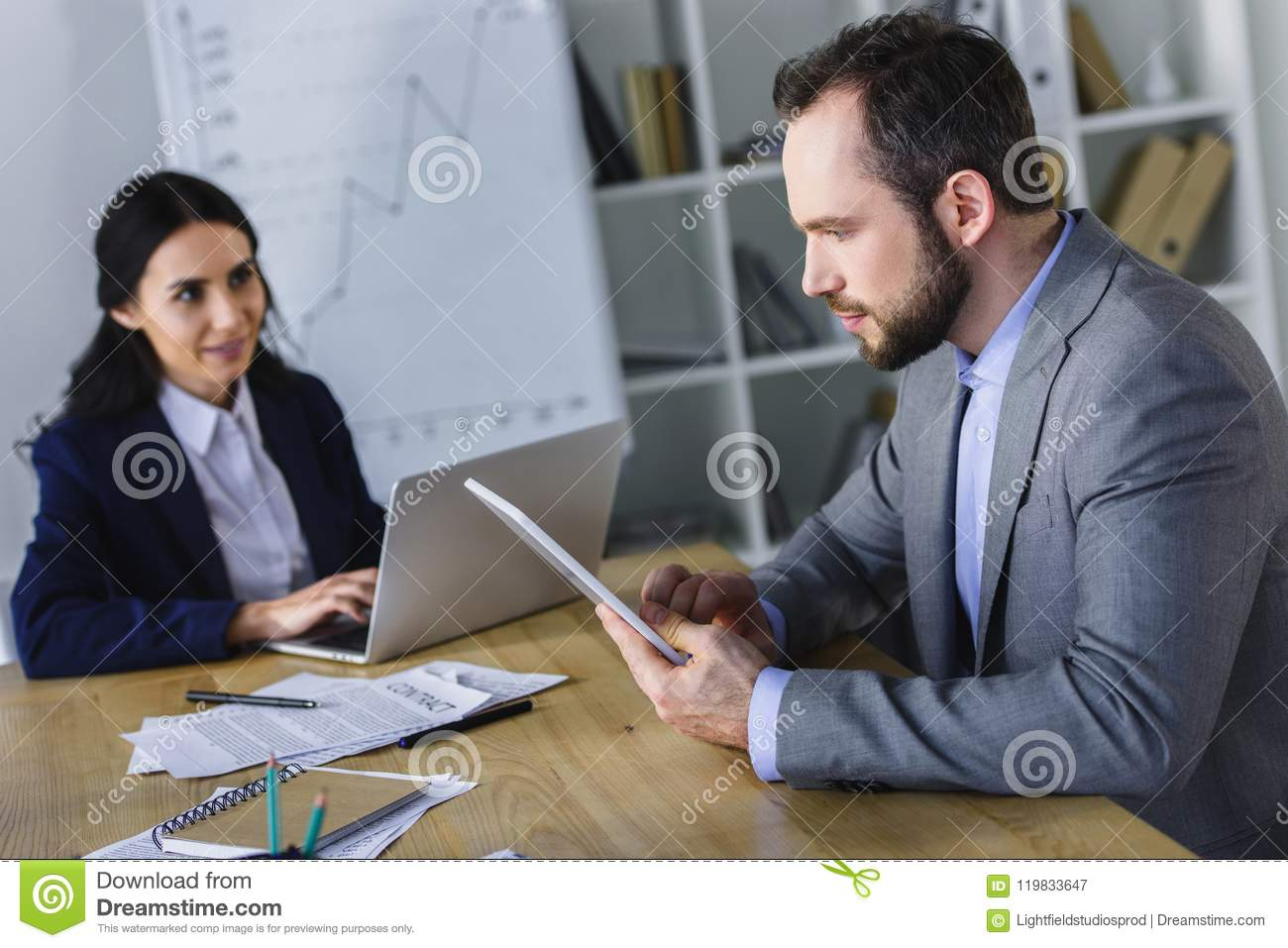 businesswoman and businessman working with laptop and tablet