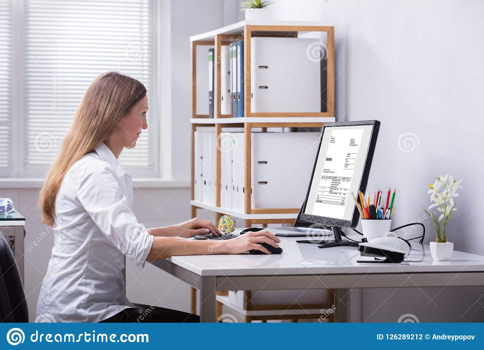 businesswoman checking invoice on computer stock photo image of