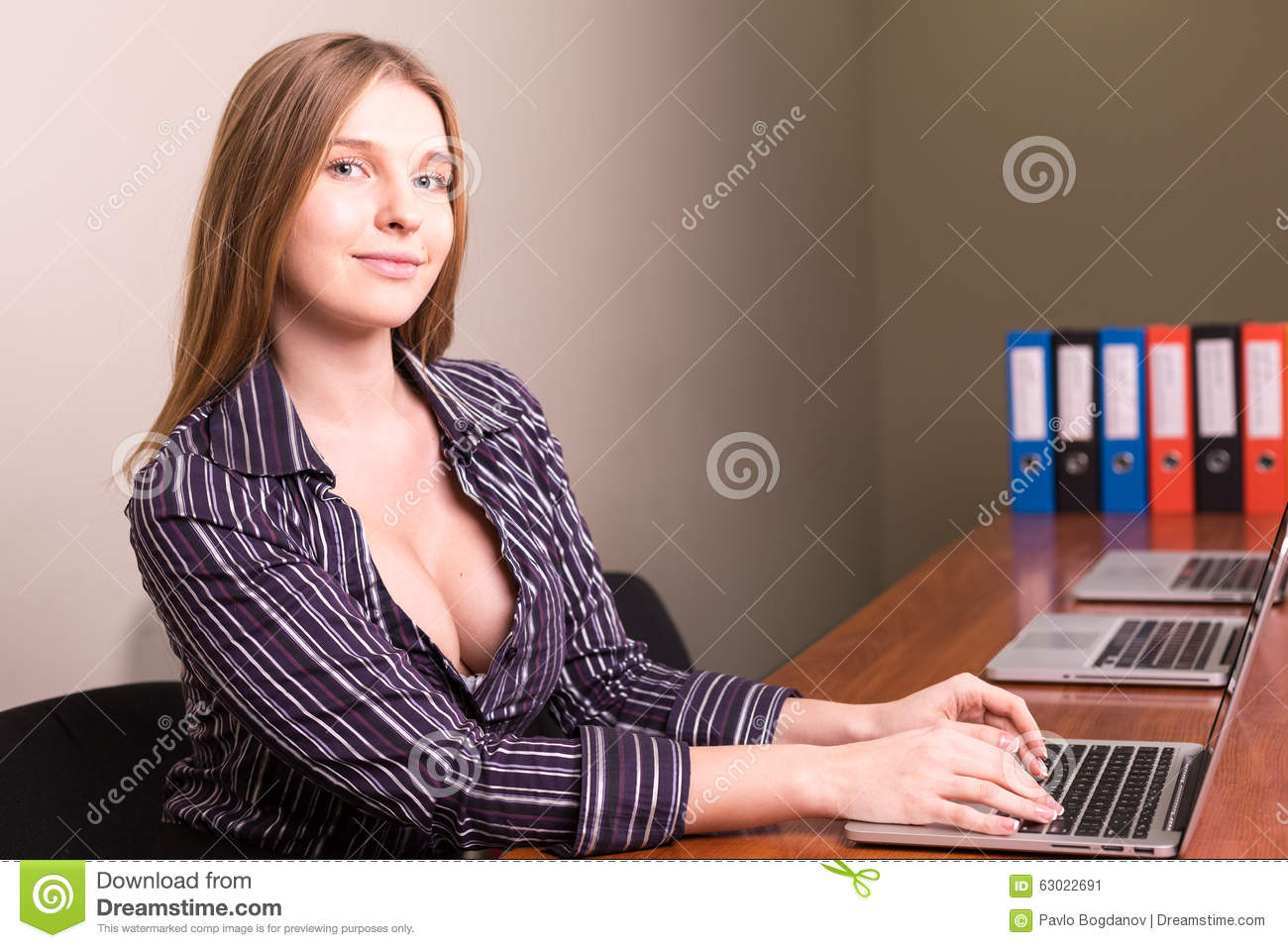 businesswoman with deep neckline working in office stock