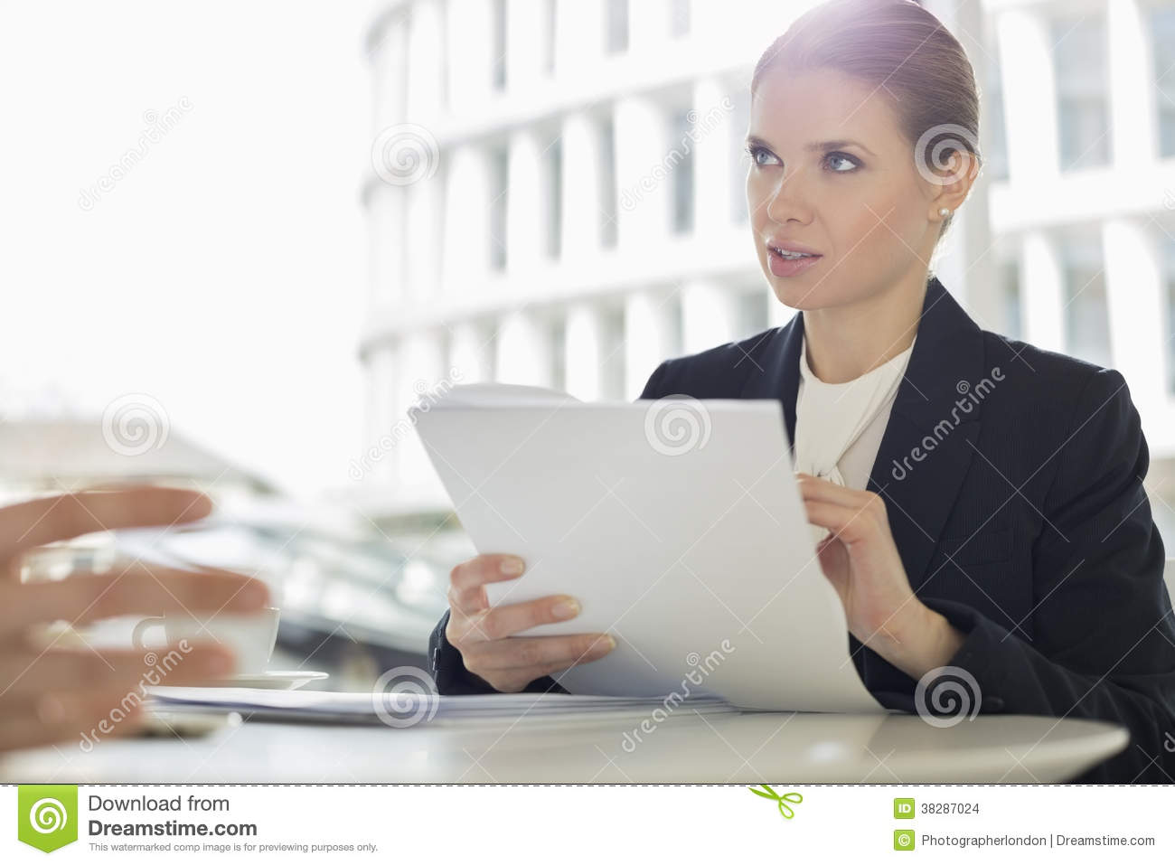 Businesswoman discussion paperwork with colleague in office cafeteria
