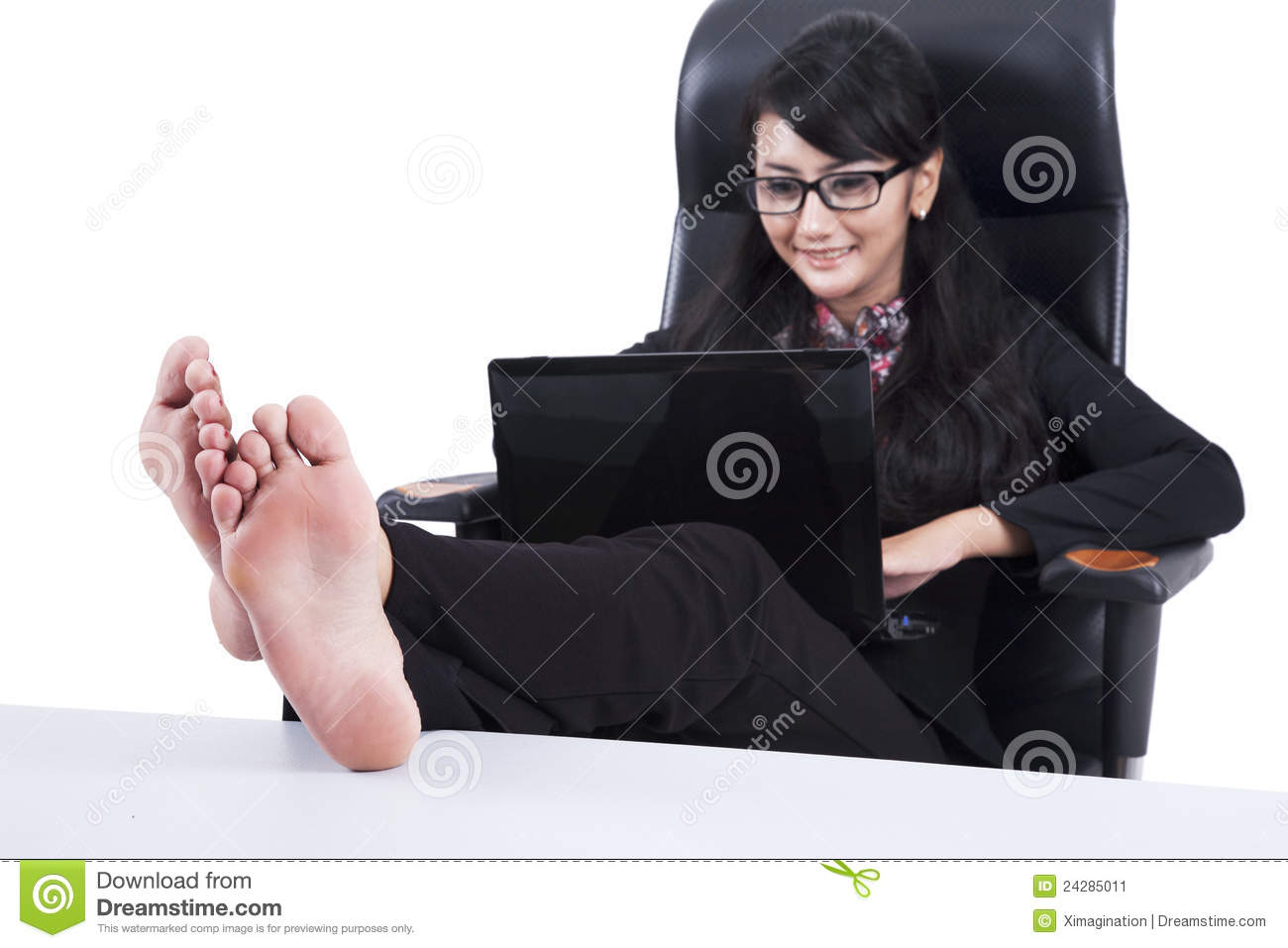 Businesswoman using laptop with Feet Up on a Table isolated on white.