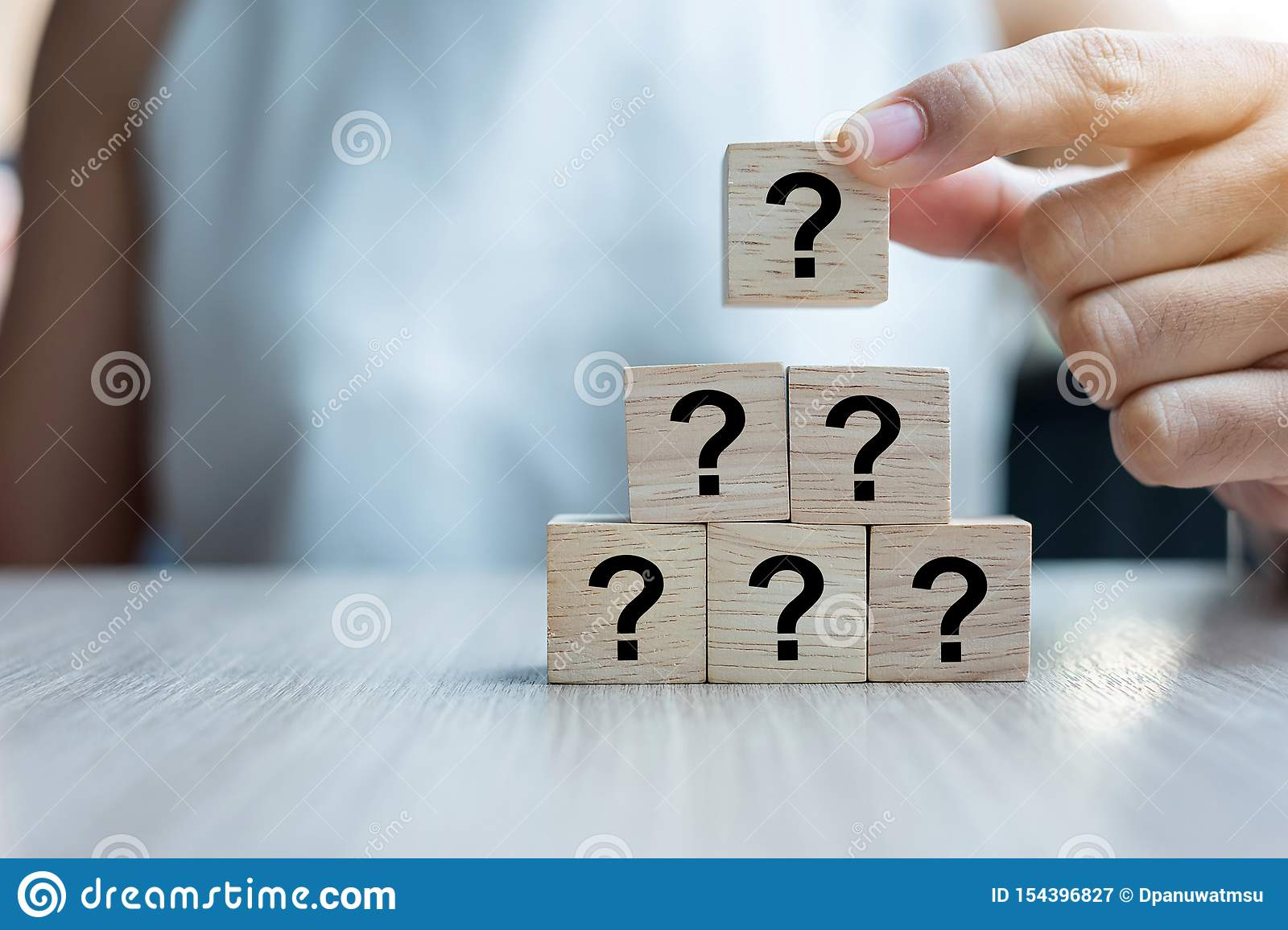 Businesswoman hand placing or pulling Questions Mark ? word with wooden cube block on the building. FAQ frequency asked