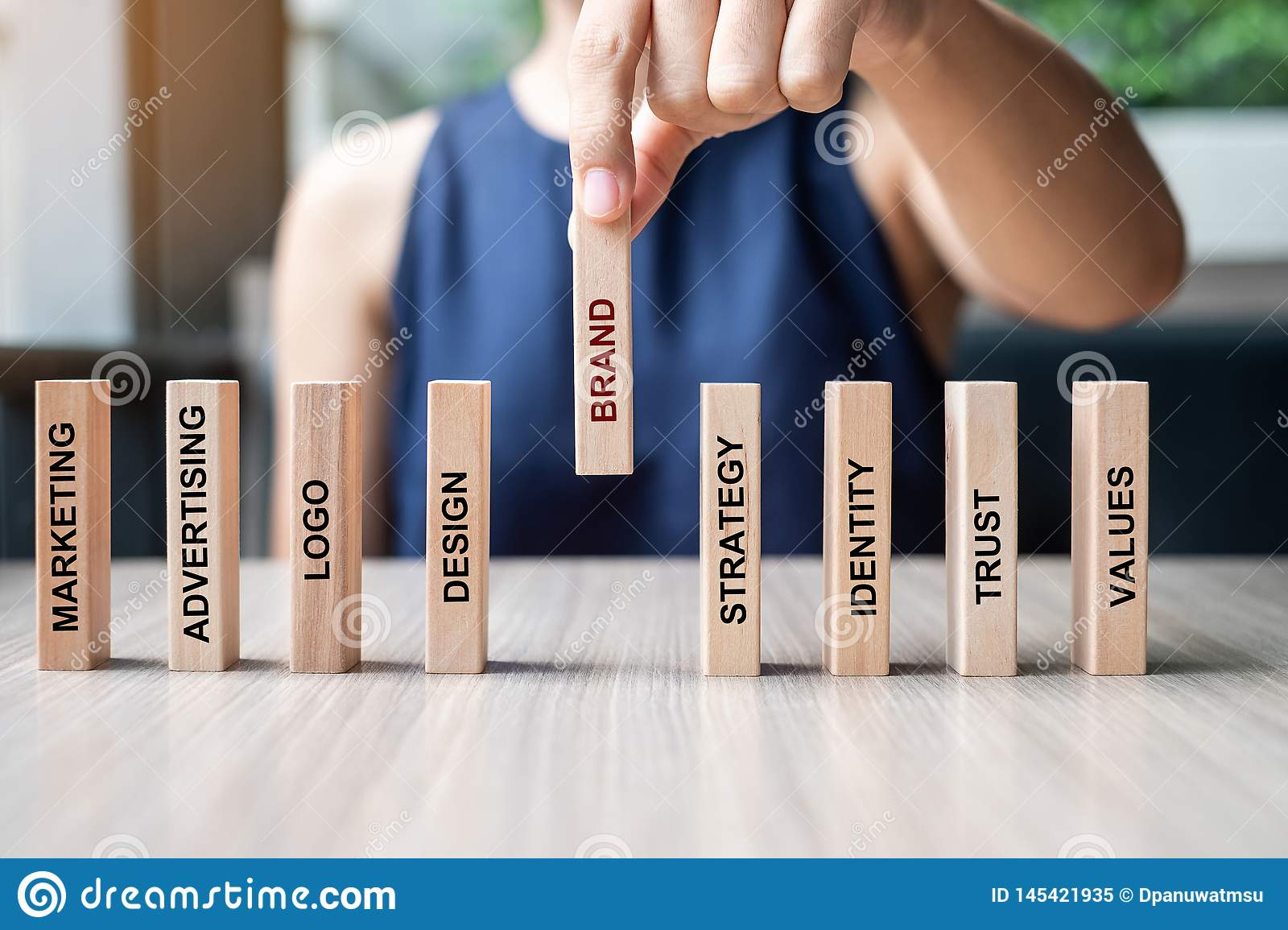 Businesswoman hand placing or pulling wooden Dominoes with BRAND text. and Marketing, Advertising, Logo, Design, Strategy,
