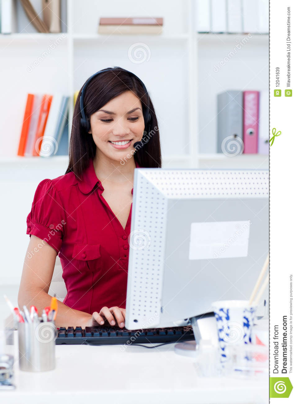 Businesswoman with headset on at a computer