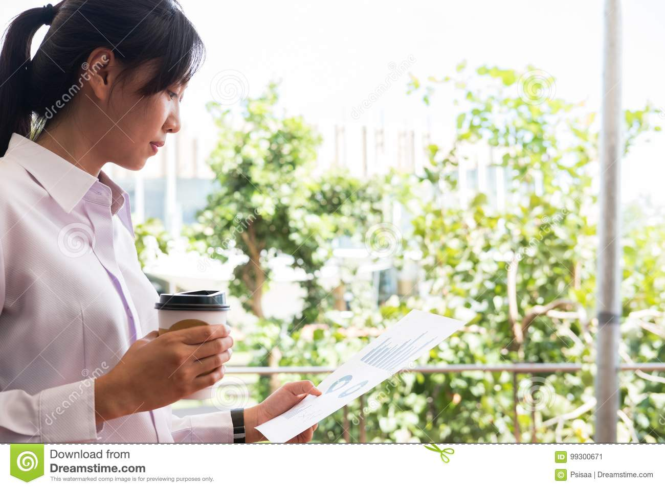 businesswoman holding coffee cup & financial summary graph outside office building. beautiful young asian woman with tea
