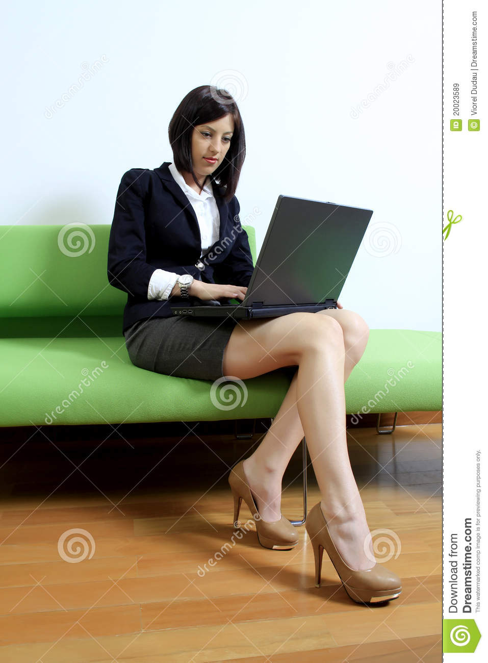 in suit with short skirt sitting on a couch using a laptop computer