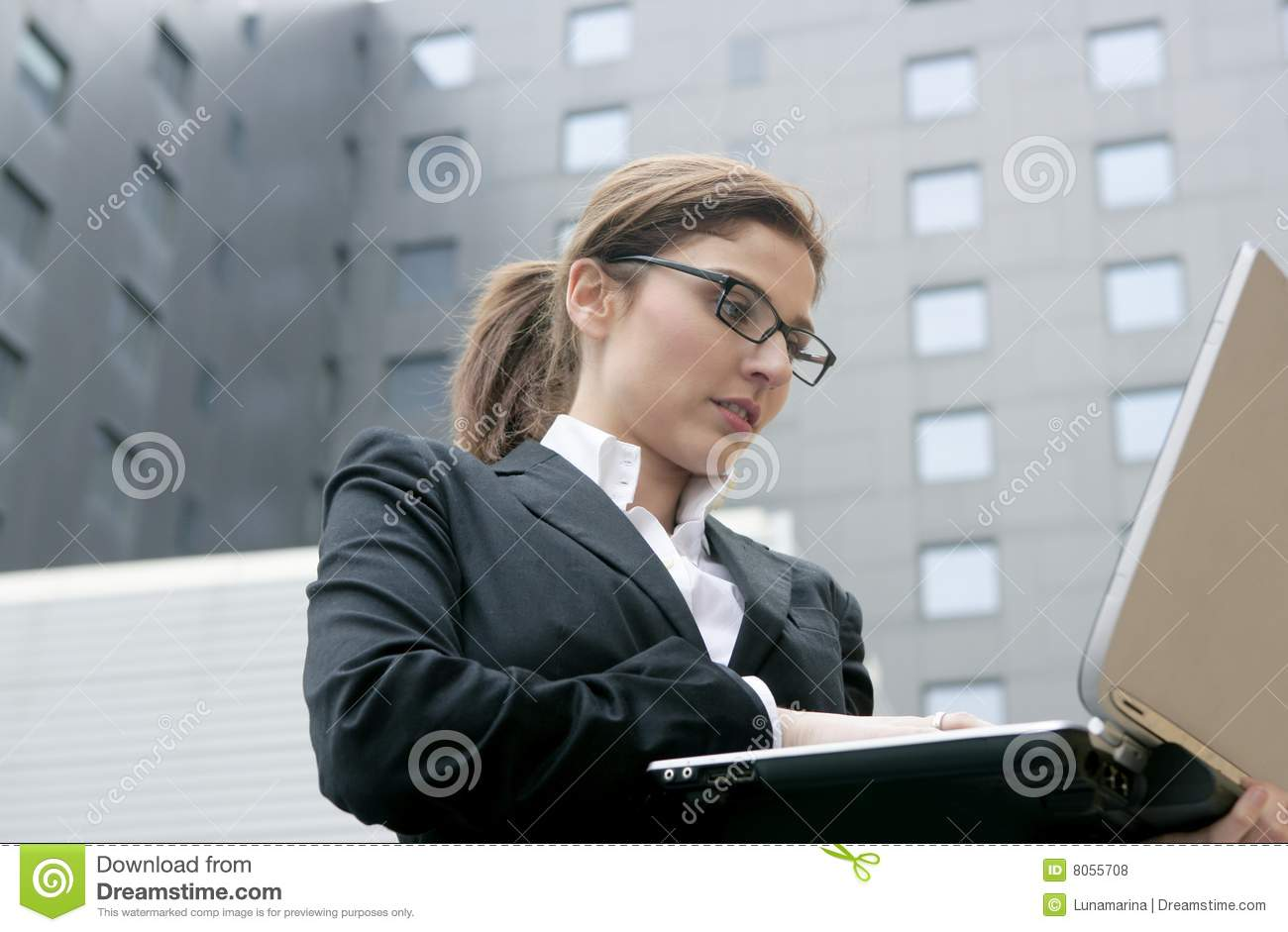 Businesswoman with laptop computer on the city