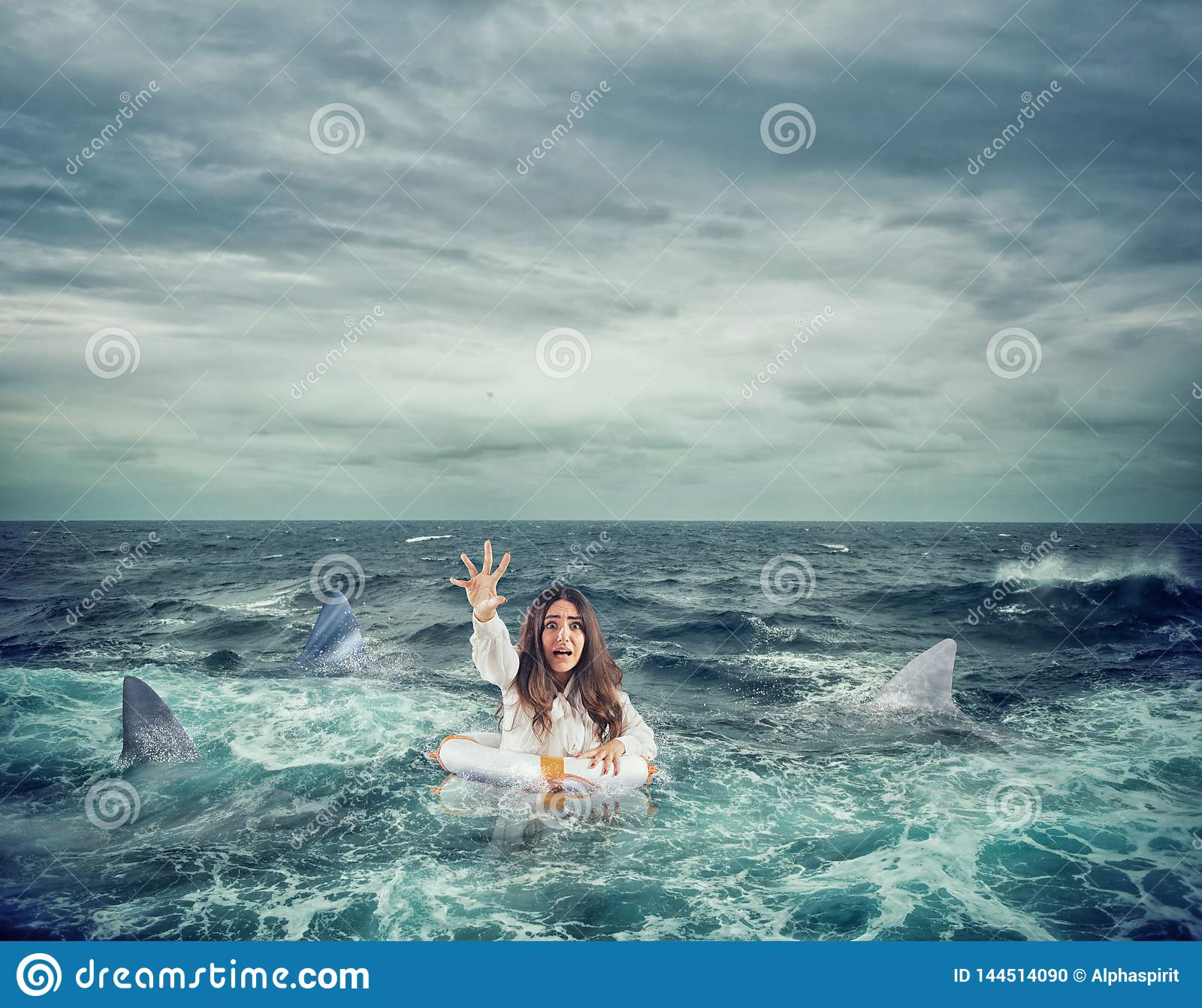Businesswoman with lifebelt surrounded by sharks asks help
