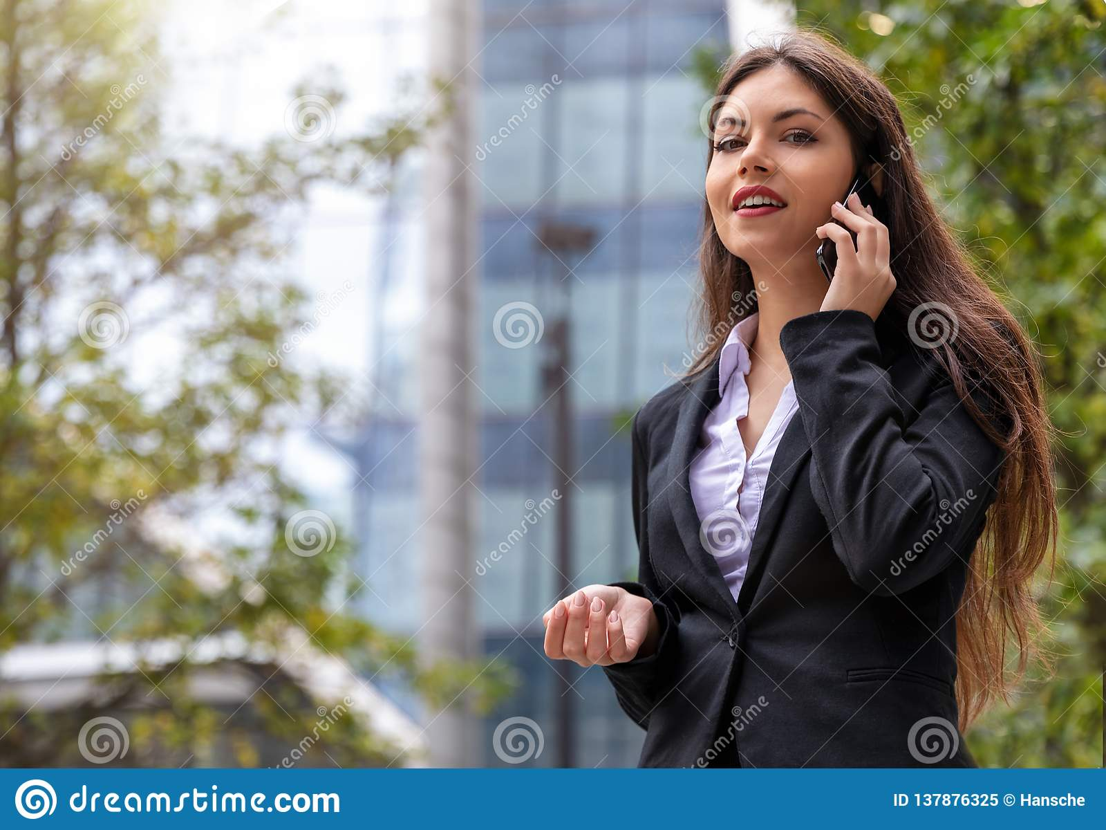 Businesswoman looking into camera outdoors in the city