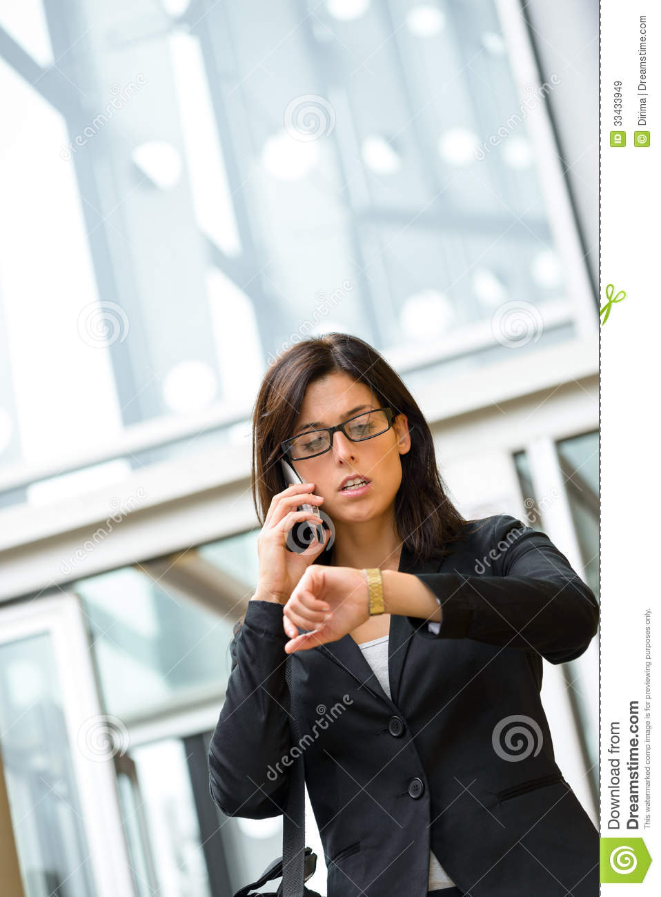 Businesswoman looking time in watch