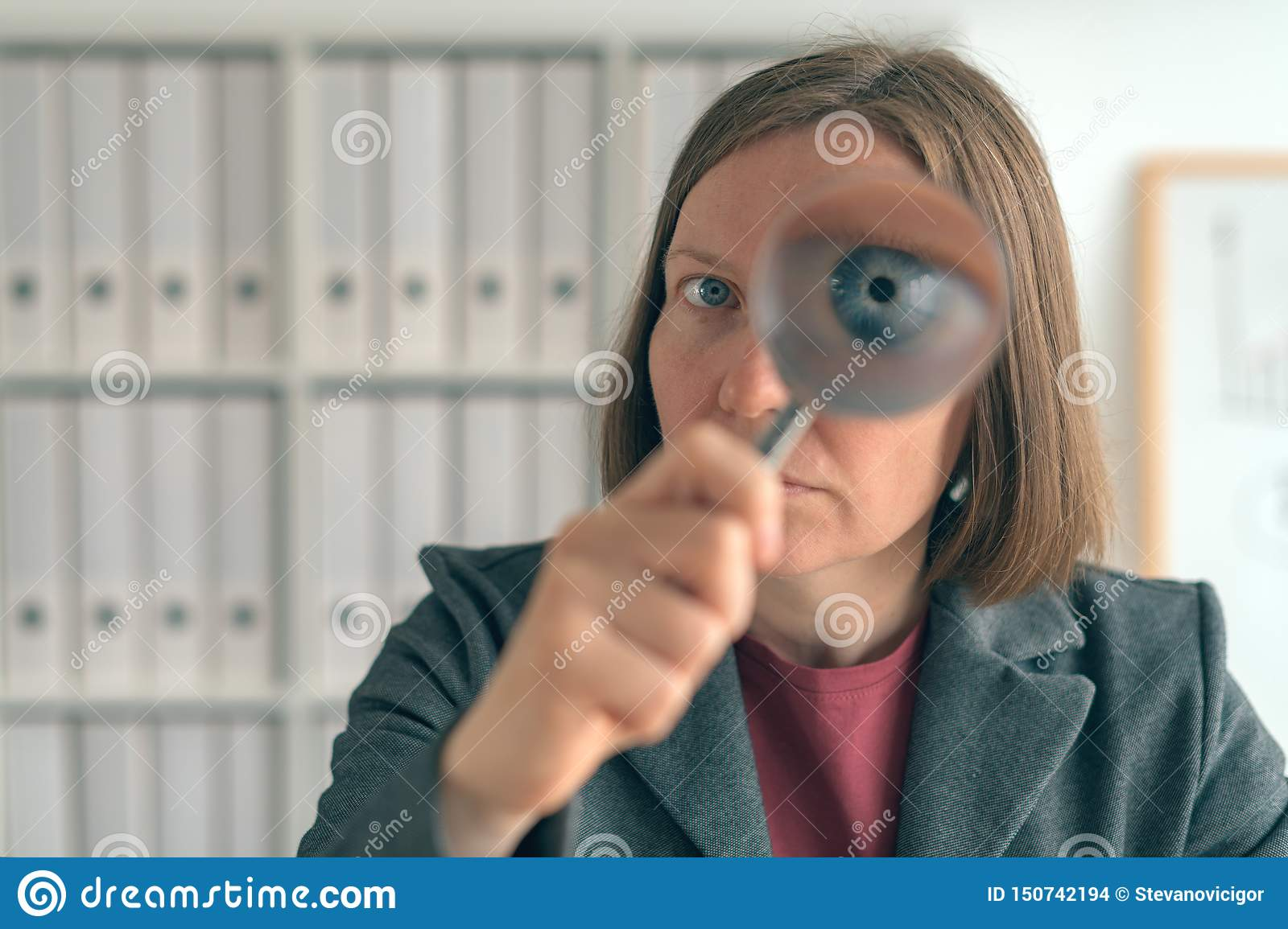 Businesswoman with magnifying glass doing business financial auditing