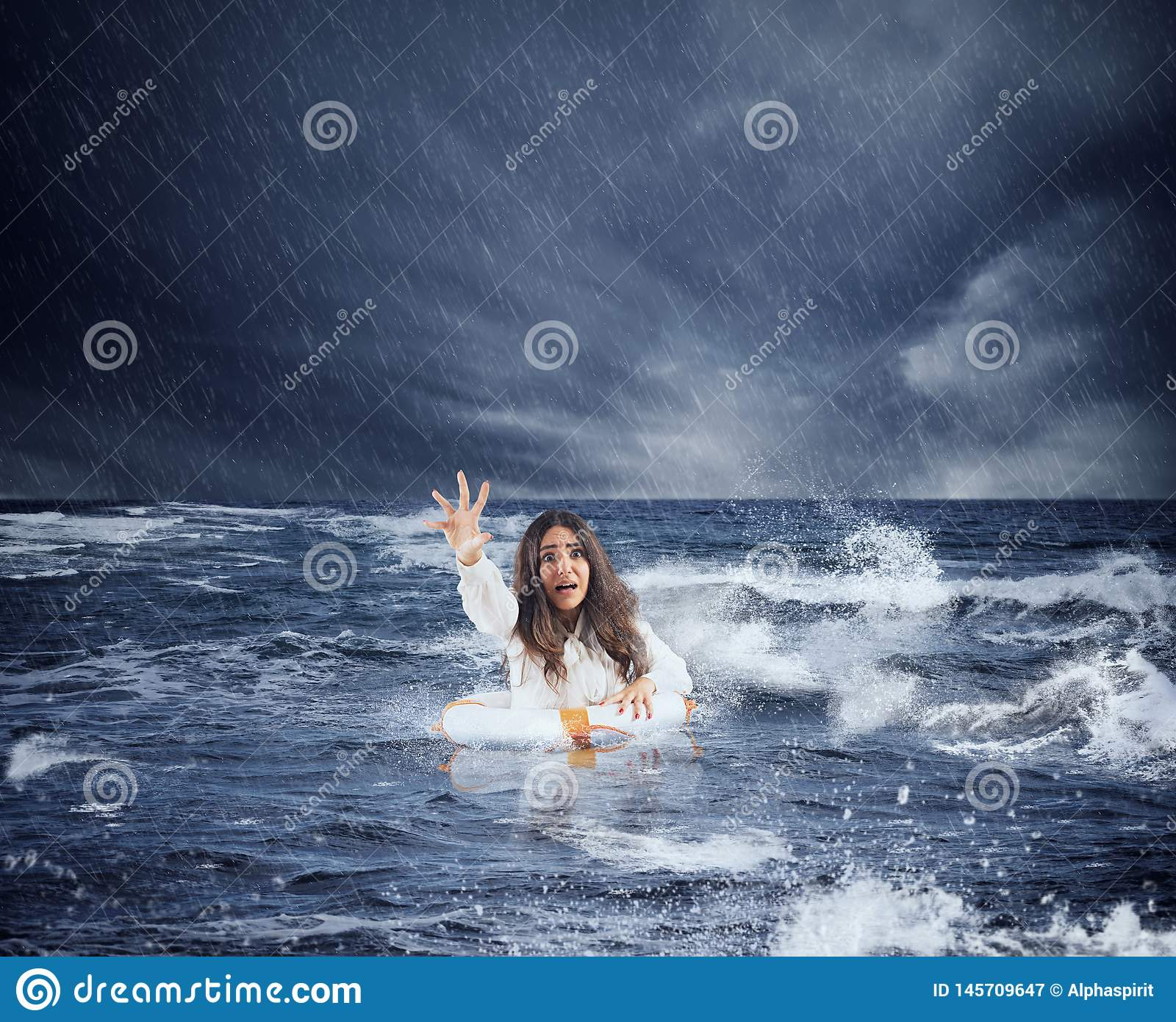 Businesswoman in the ocean with lifebelt asks help during a storm