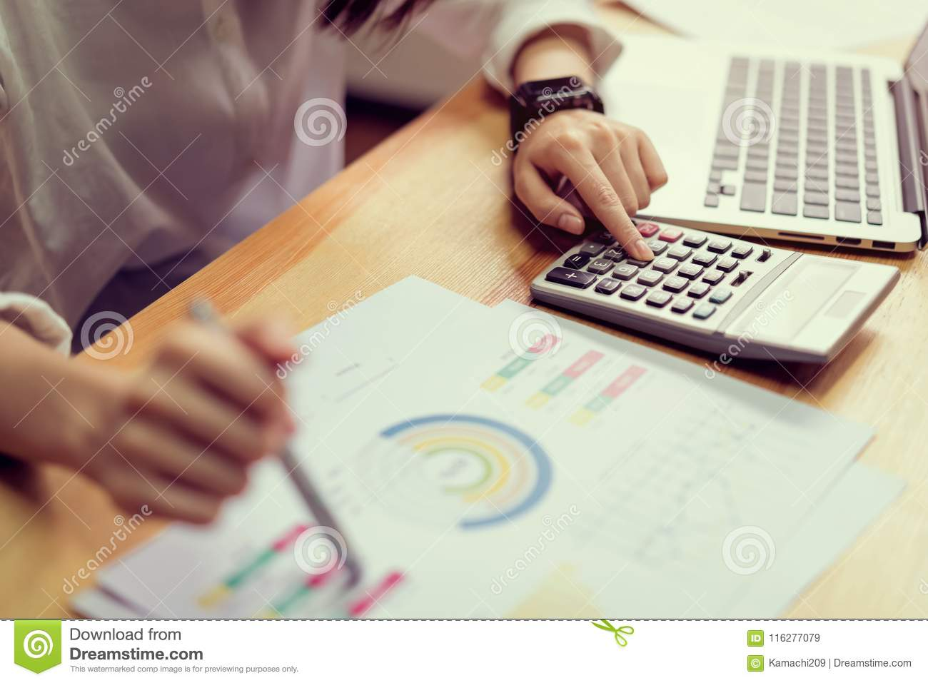 Businesswoman in office and use computer and calculator to perform financial accounting.
