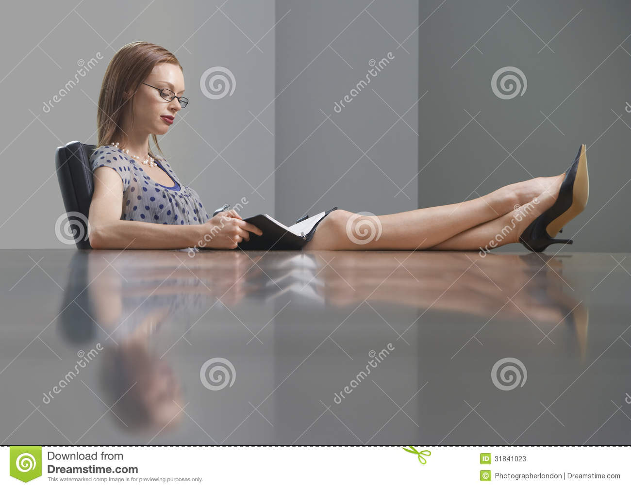 Businesswoman Reading Book With Feet On Conference Table