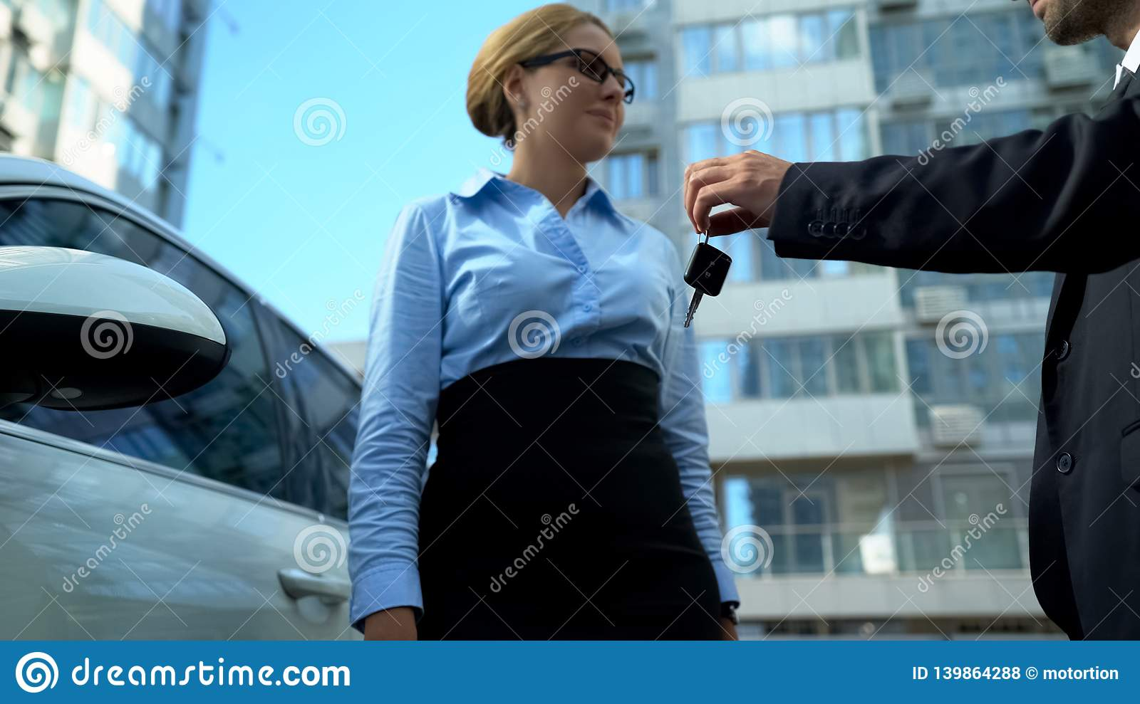 Businesswoman receiving keys to luxury auto from dealer, car loan or purchase